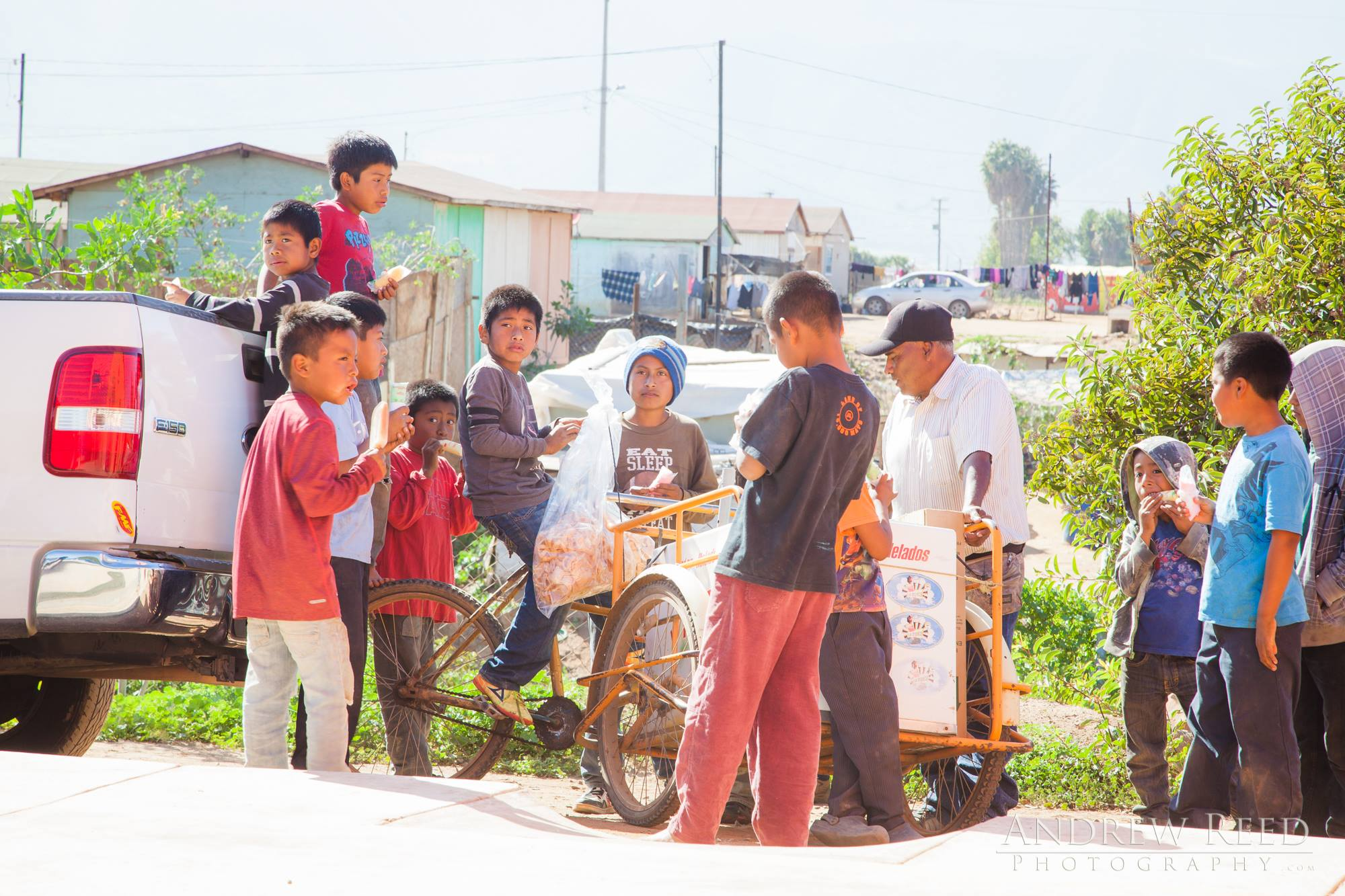 Some of the children having ice cream while Marco reminds them to keep things clean and to wear their shoes. Lack of cleanliness in these villages can lead to sickness and death and Marco is trying to break the cycle.