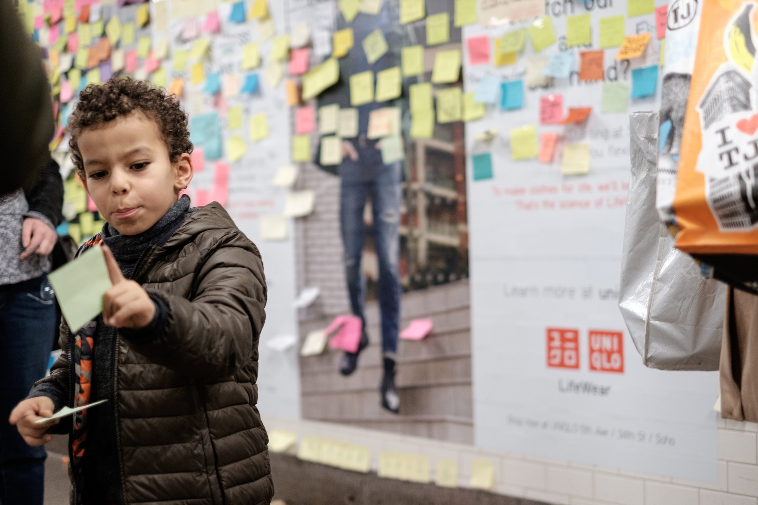 A child readies a post-it of peace for the wall