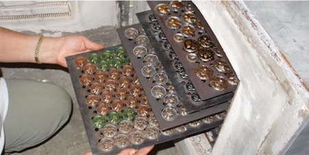 After finish, trays of buttons are returned for one final intense heating to fire-polish and seal the work.