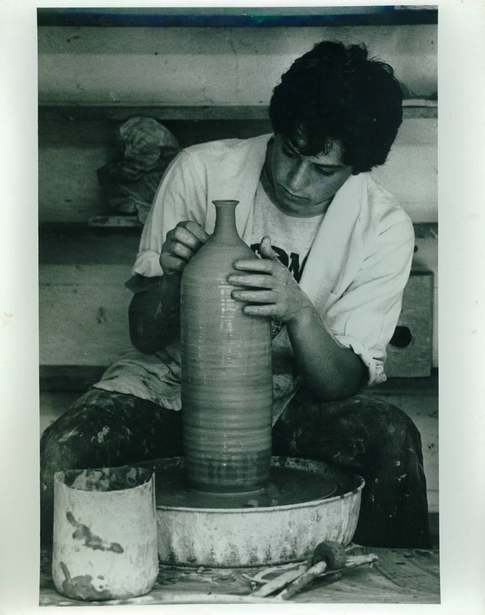 A young, clay-spattered Jonathan at the potter's wheel.