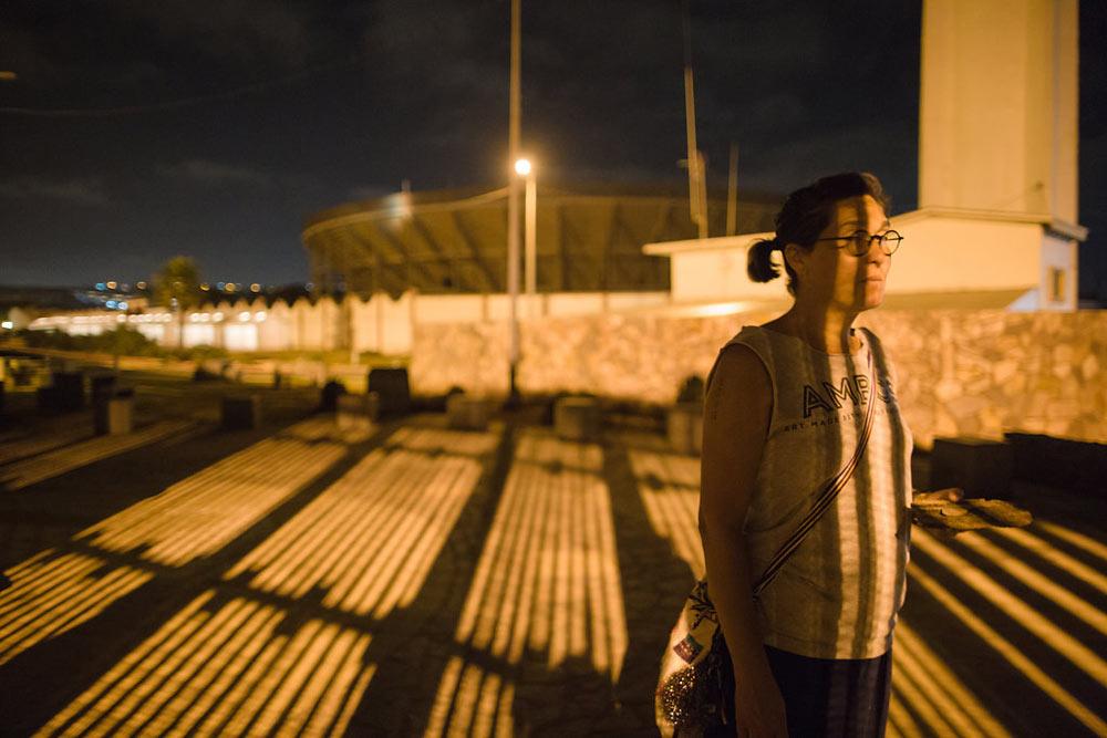 Tanya stands at the border wall. Photo by Gina Clyne Photography.