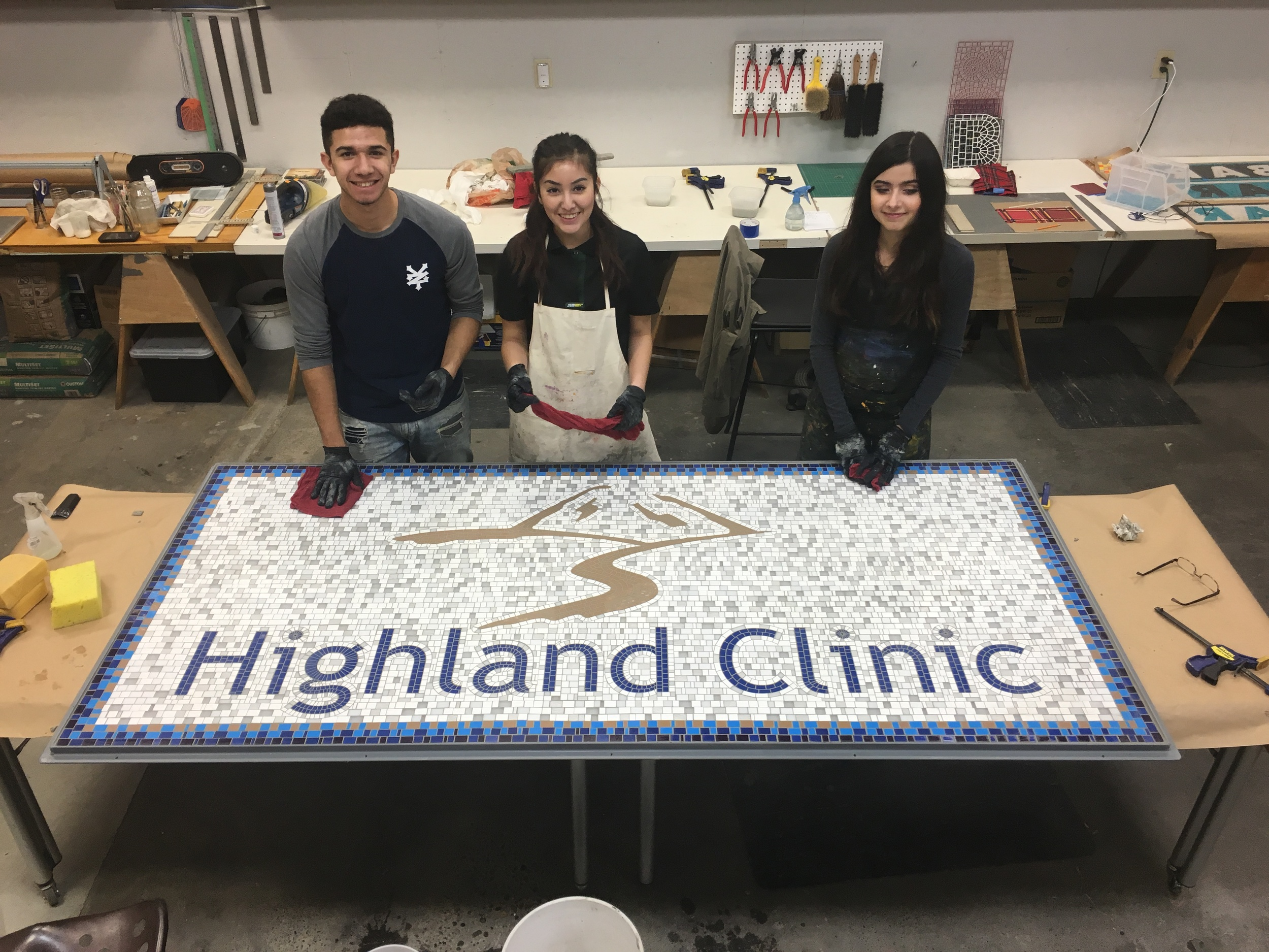 The finished sign with studio apprentices Saul, Lilly and Amparo