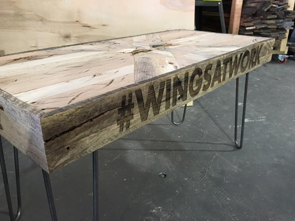 Conference table in production with corporate Red Bull logo and event hashtag #wingsatwork etched by CO2 laser