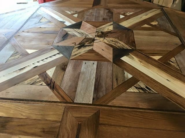 The main conference table took center stage with a blend of reclaimed oak, acacia, and red woods patterned in a center starburst and side Celtic motif