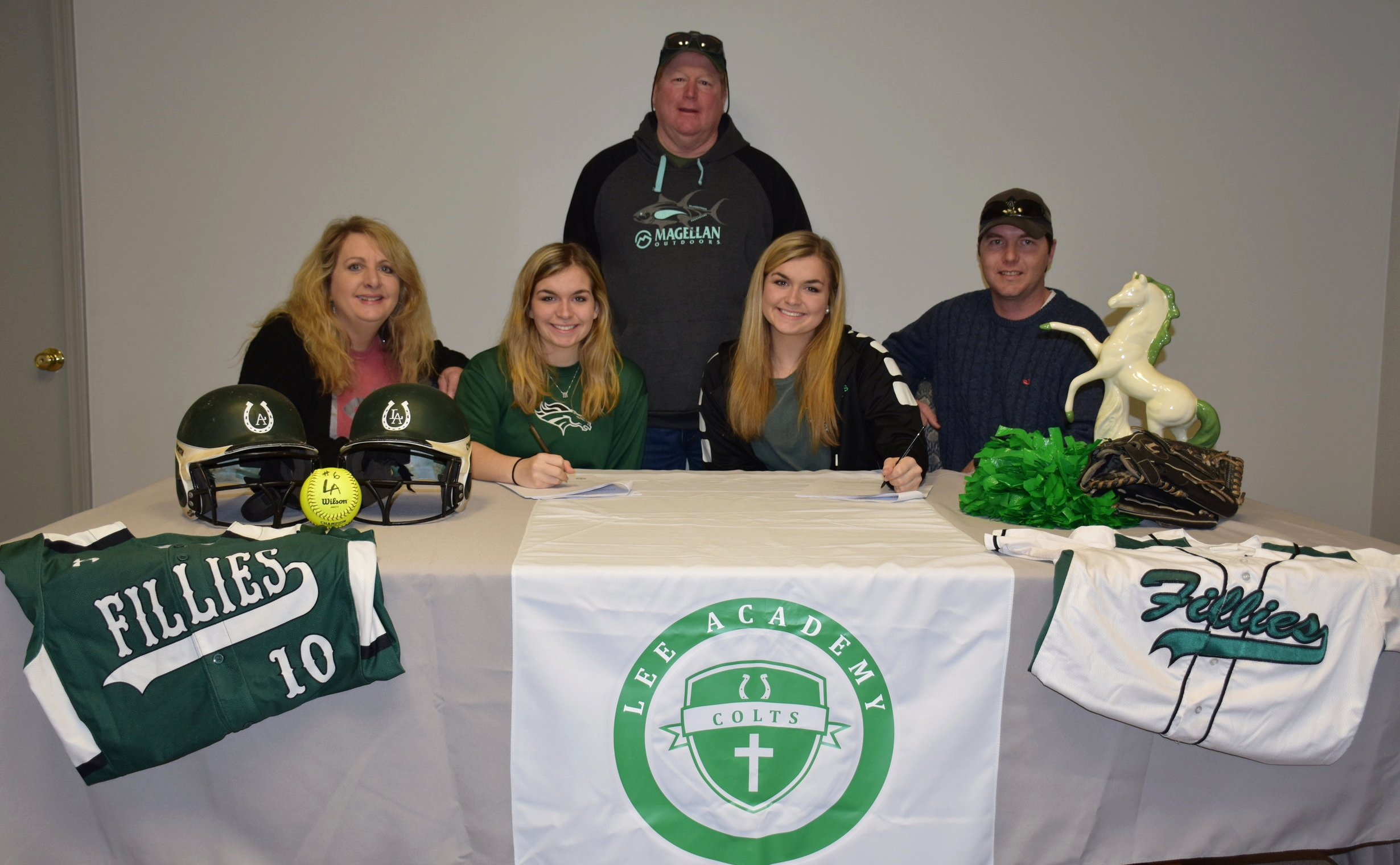 Maddie and Sydni Moore seated with their parents Karen and Jay Moore. Head softball coach, Tom Fleming standing.