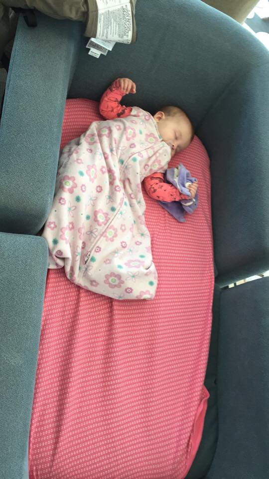 "Our daughter sleeping in a ""crib"" we made by pushing two chairs together."