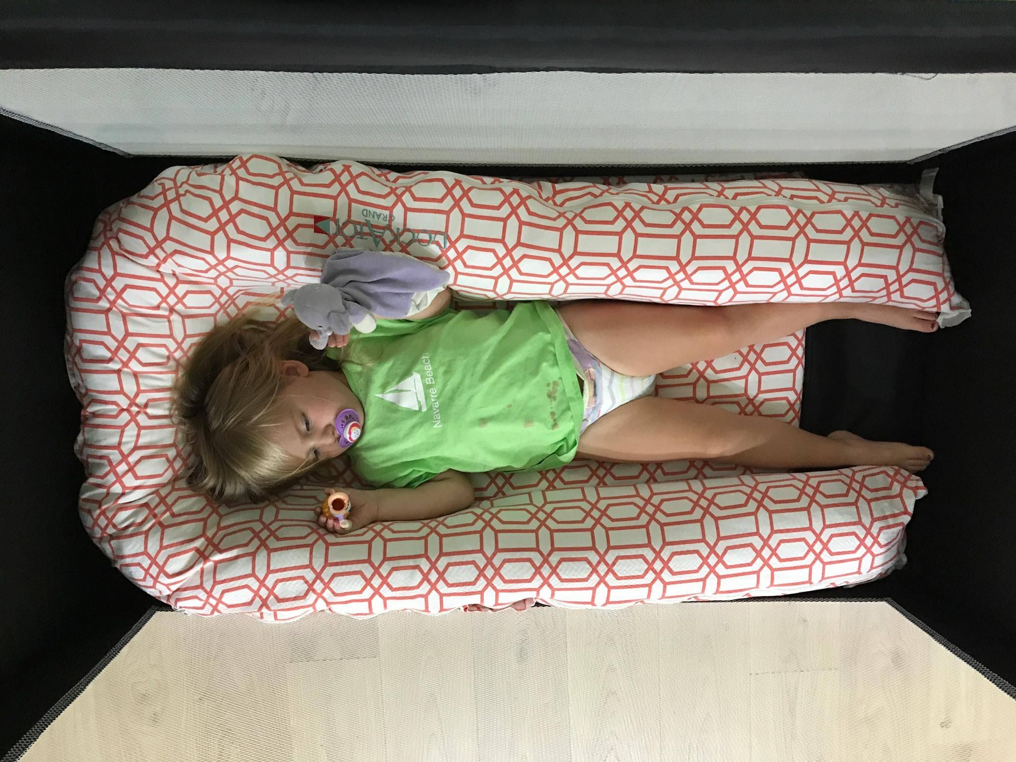 Charletta at 2 years, 4 months in an extended length travel cot -- she can fully extend her legs and sleep on her stomach. (also, don't pay attention to her stained tshirt)