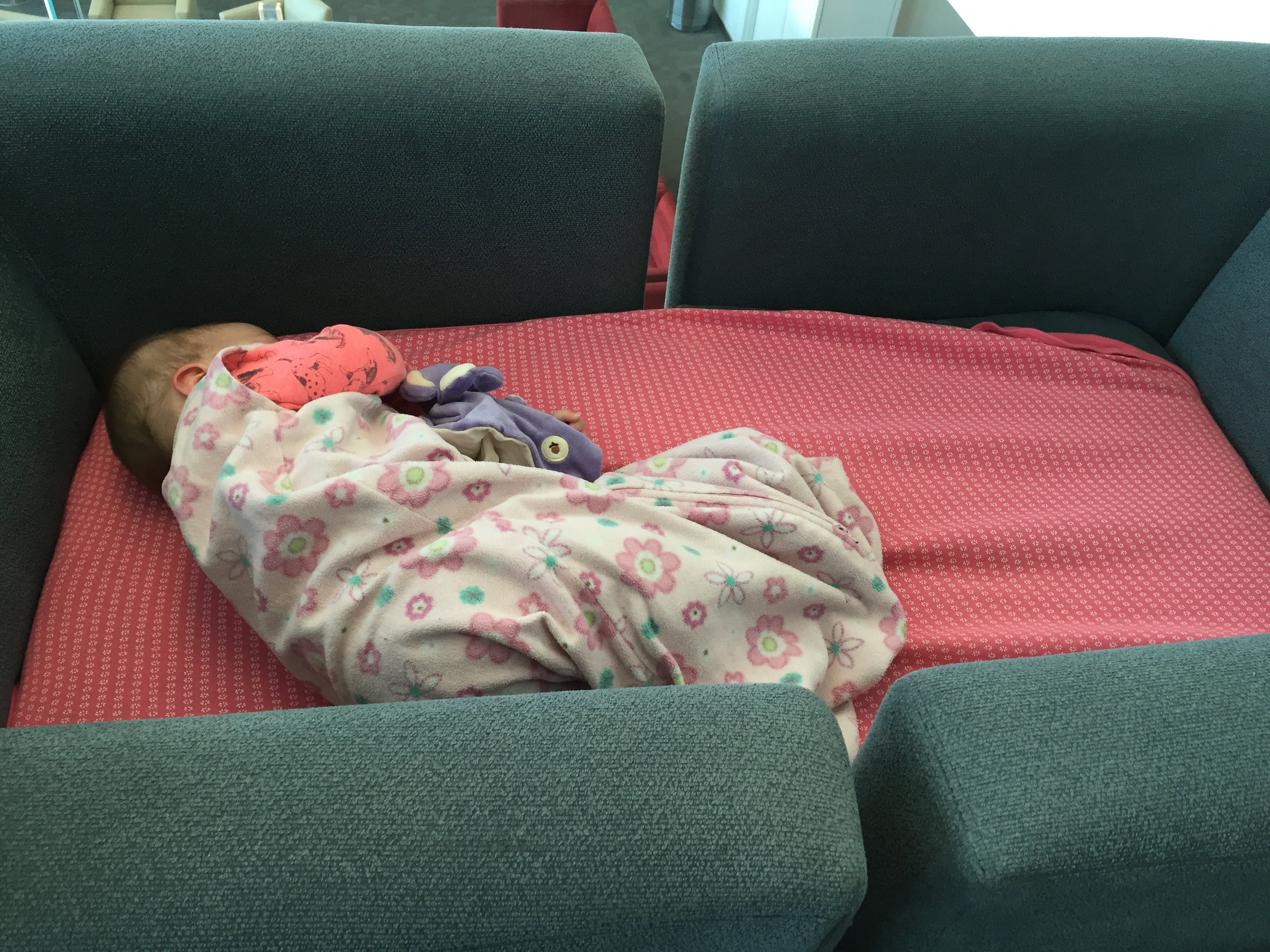 Our daughter, age 6 months, sleeping in a bed we made by pulling to chairs together in the international lounge in atlanta