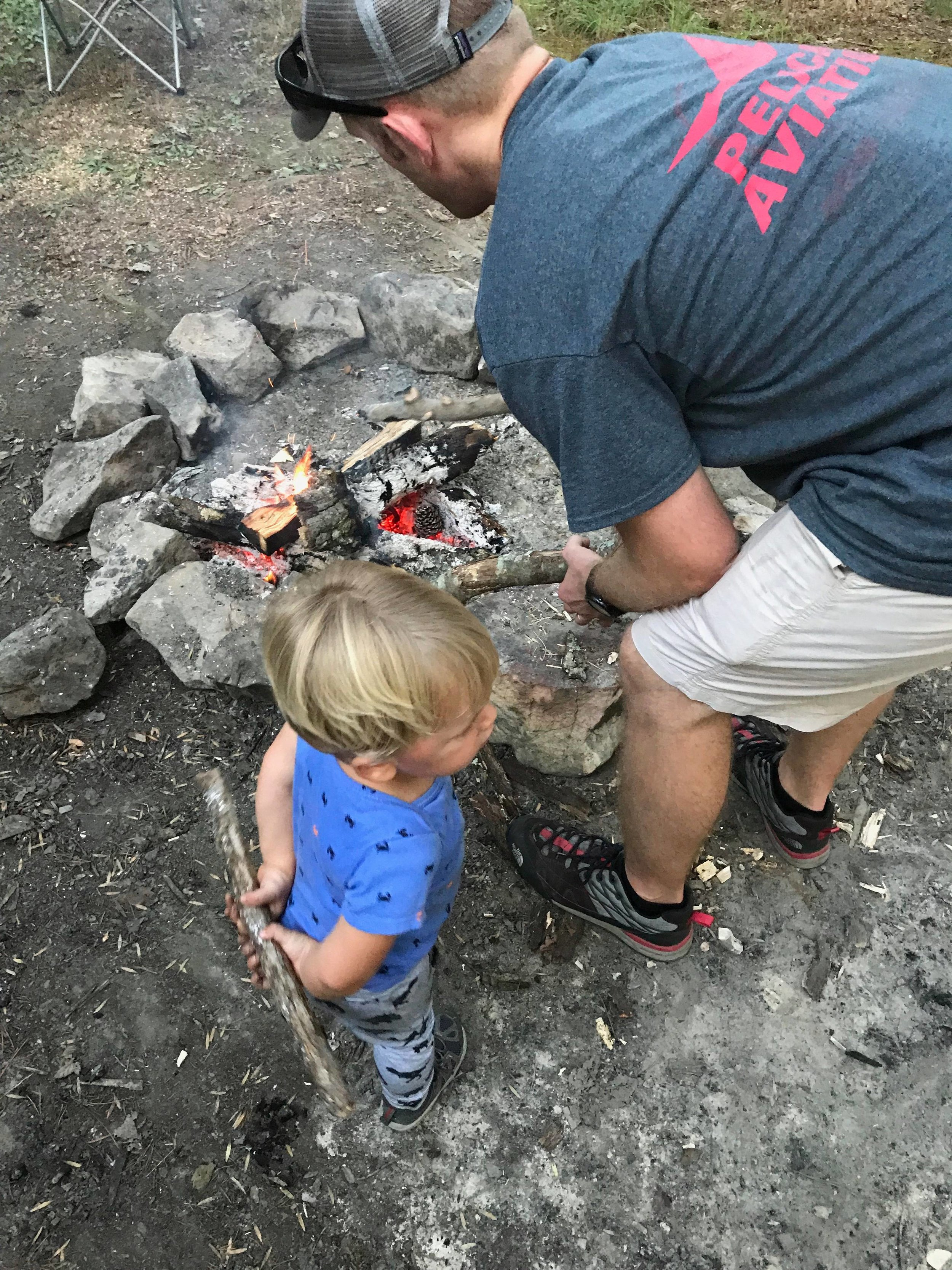 Latham helping daddy get sticks and start the fire