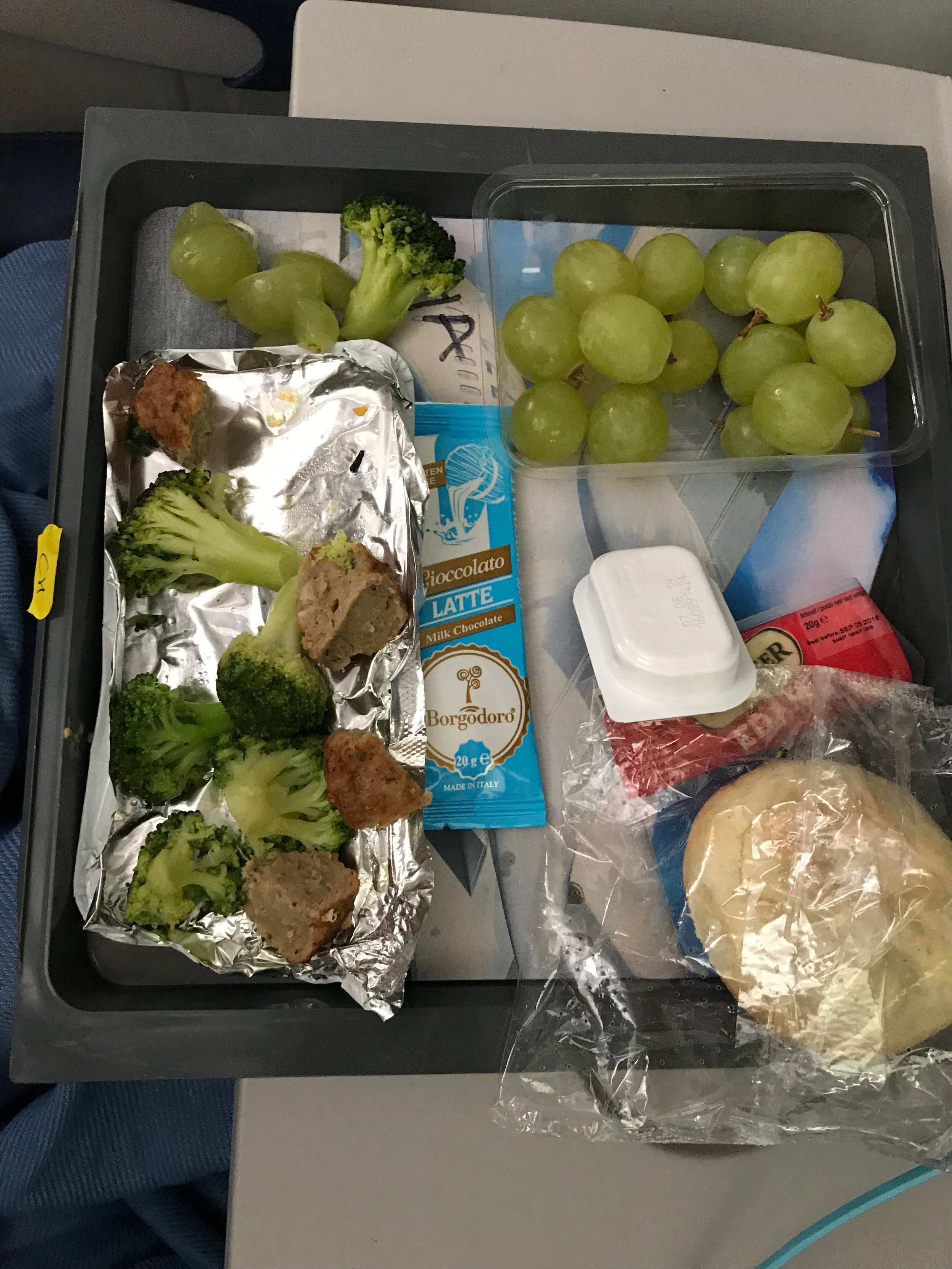 This meal was broccoli, meatballs, grapes, bread with cheese and a dessert.