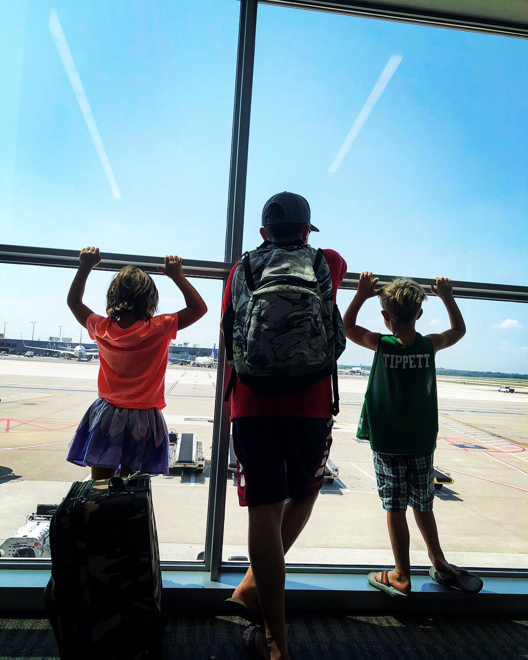 Hudson and two of his siblings watching the plane come in before he boarding his flight. His siblings get to some sit with him unti he boards!