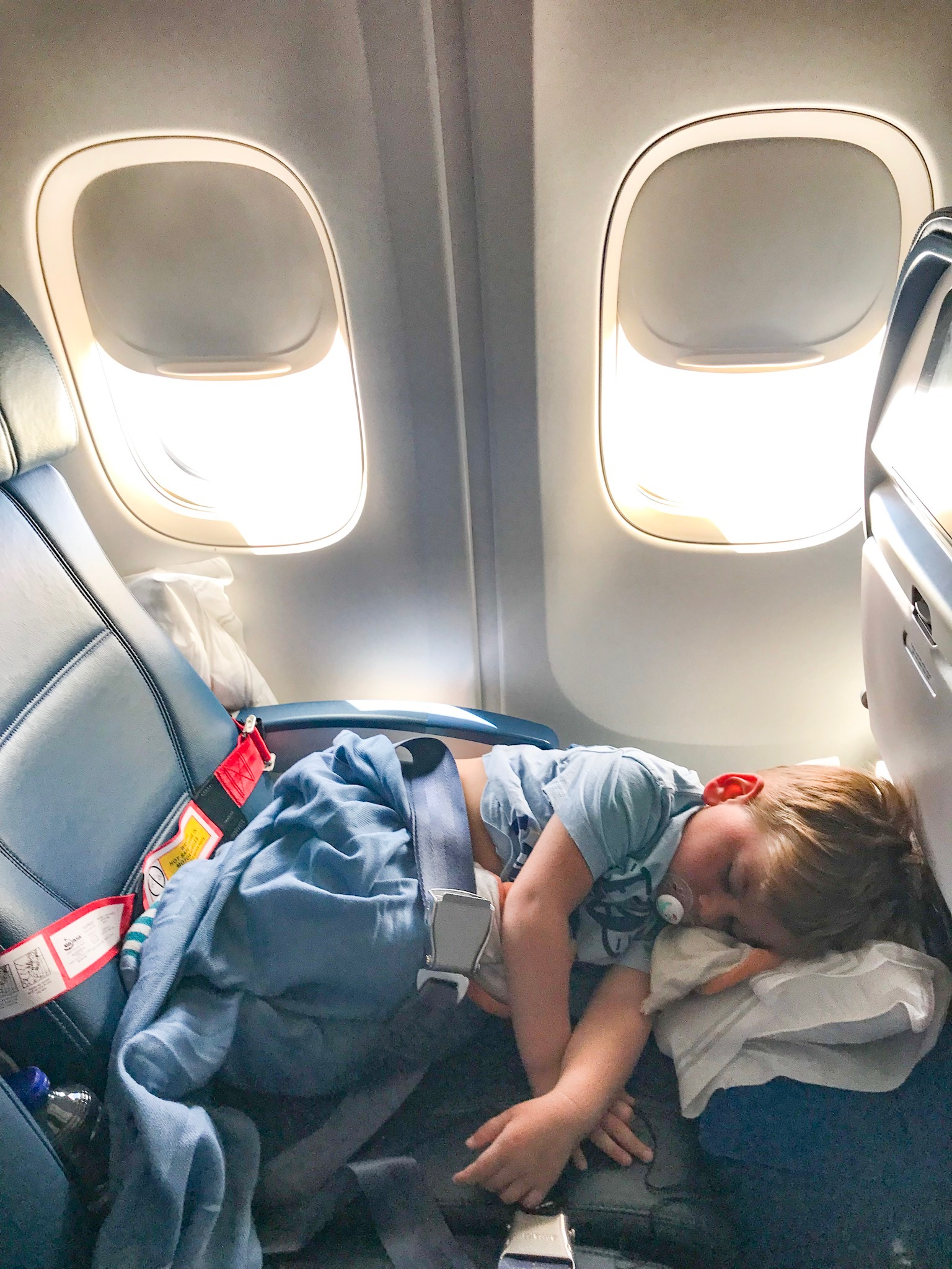 My son using his inflatable pillow to take a nap on our Day flight from Rome to Detroit