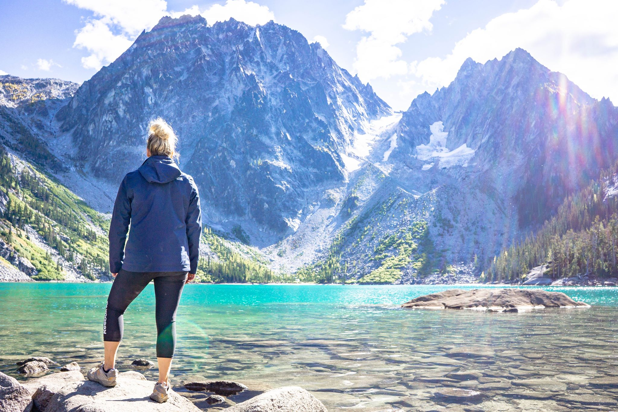 This photo is of me standing at colchuck lake in Washington. I was able to fly to Spokane from Florida with both my kids for only $500 — I used the companion certificate offered through the delta reserve card. I bought my tickets & charletta's was free. Latham was a lap infant (23 months) so he was free, but i could have gotten his ticket with miles.