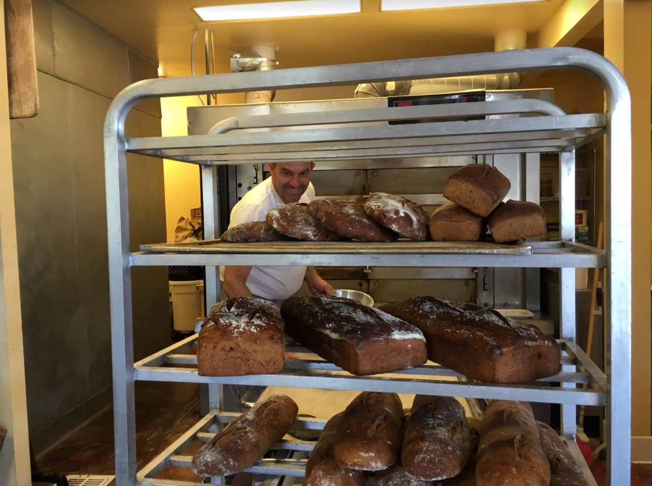 Joseph Abrakjian at Seed Bakery removing those loaves fresh from the bread oven.