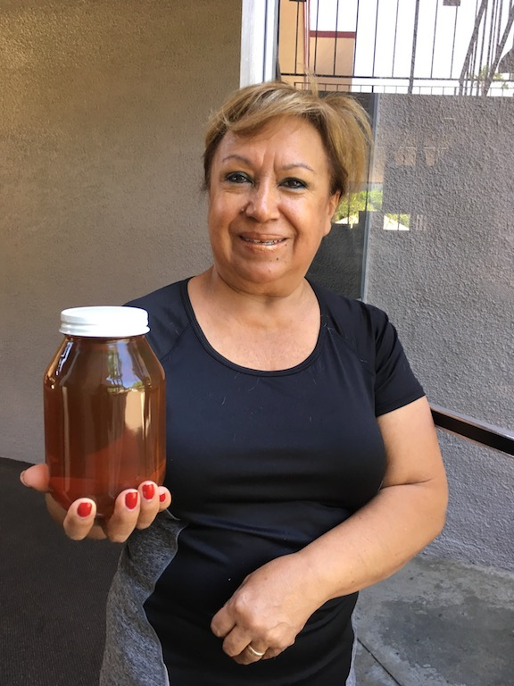 Martha holding a jar of her father-in-law Victor Jaramillo's honey.