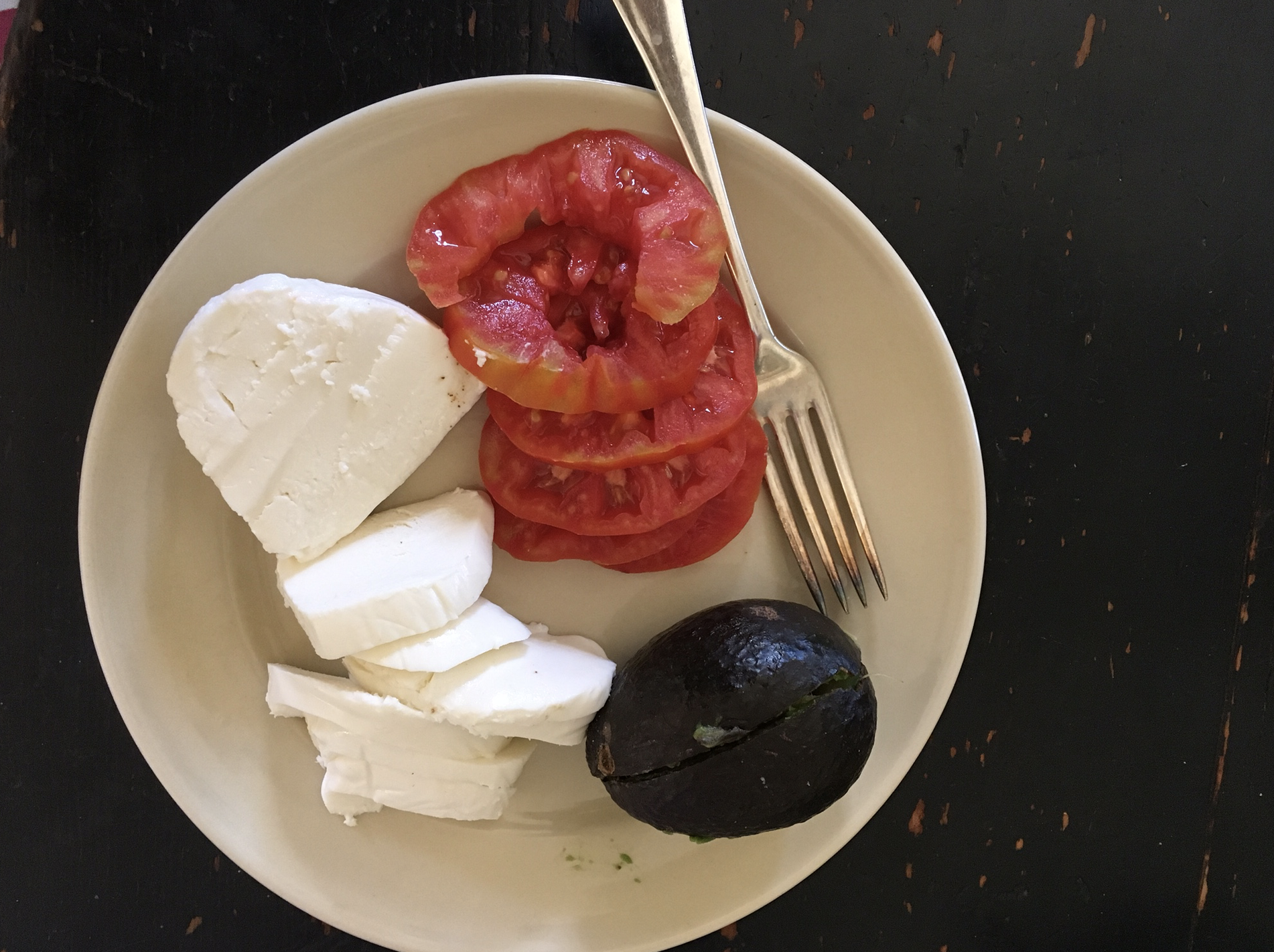 A very, very ripe tomato and avocado caught in the nick of time with fresh mozzarella.