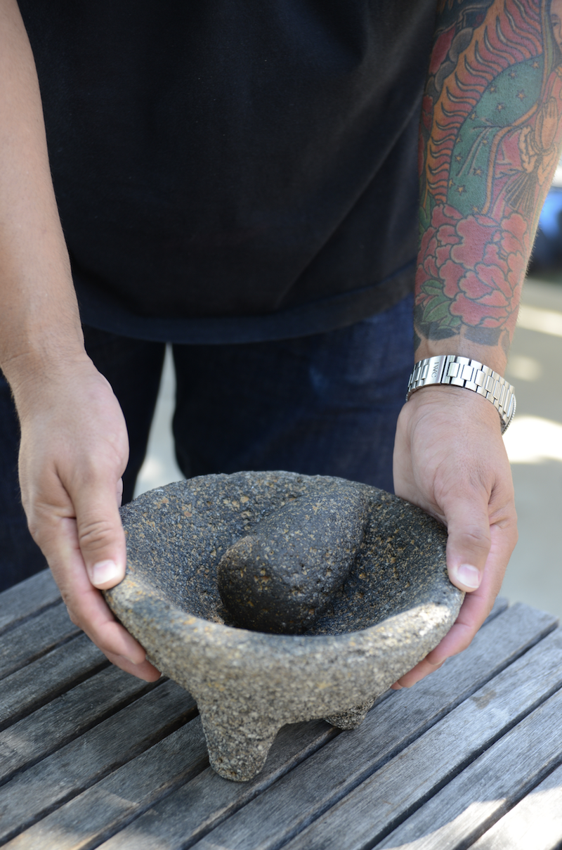 Mario Rodriguez holding his mother's molcajete, passed down from his grandmother. The patina created by traces of ground spice is a part of its beauty.  Photo by  Ann Cutting.