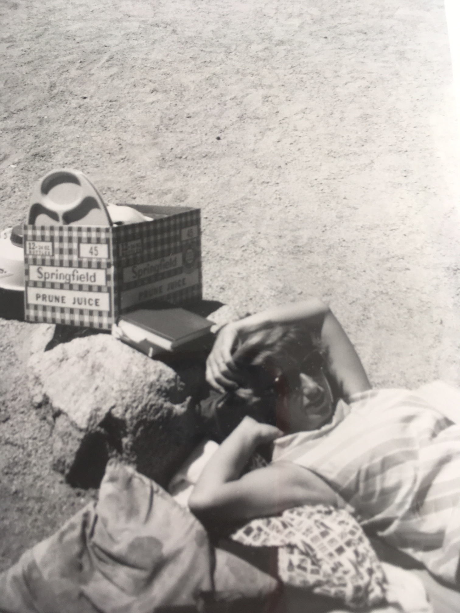 Stepmom Margie resting with some camping gear behind her, circa 1958.