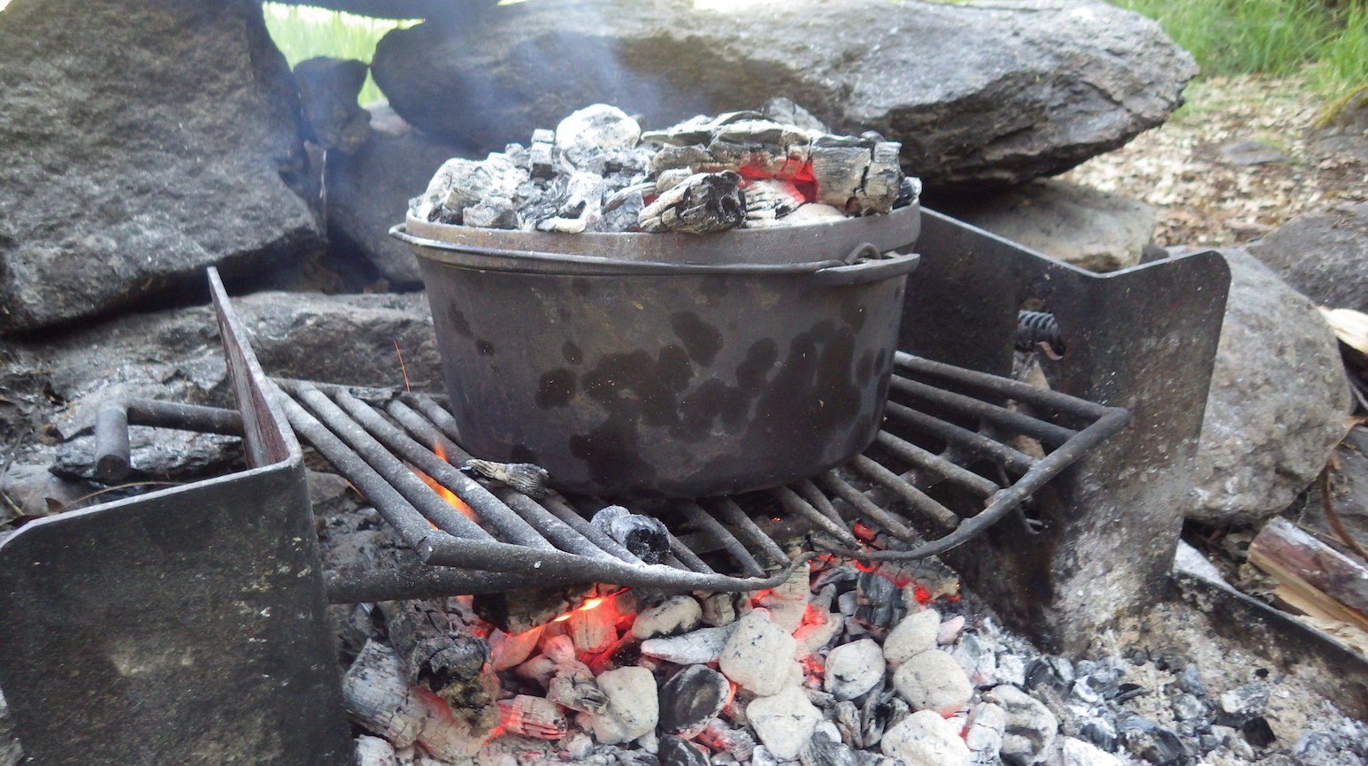 Dutch Oven Biscuits baking over an open flame.