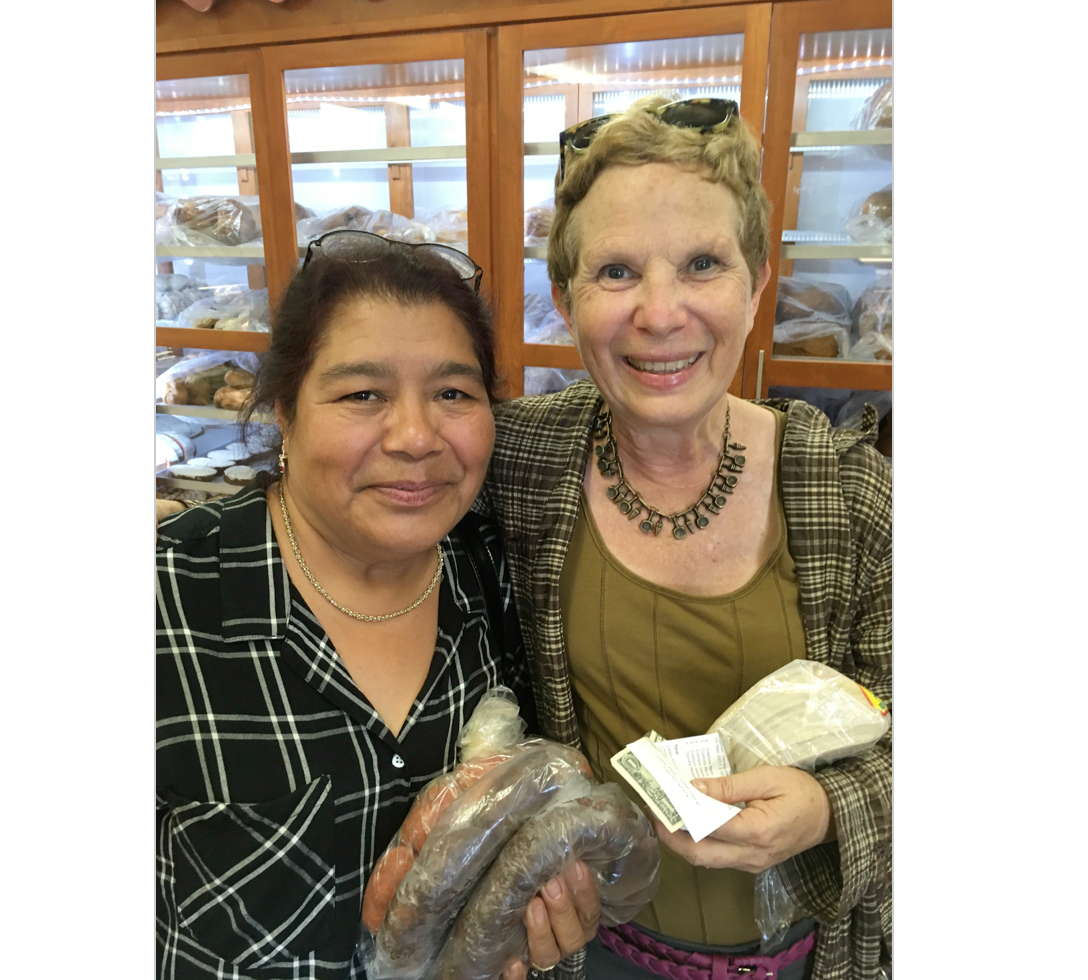 Marina Lopez at La Mayordomia buying family feast ingredients;chorizo and morcilla. Her husband was carrying a 10-pound bag of fresh masa. On the spot, she invited me to come and help cook and learn. I plan to. I am holding the packaged tortillas – wrong!