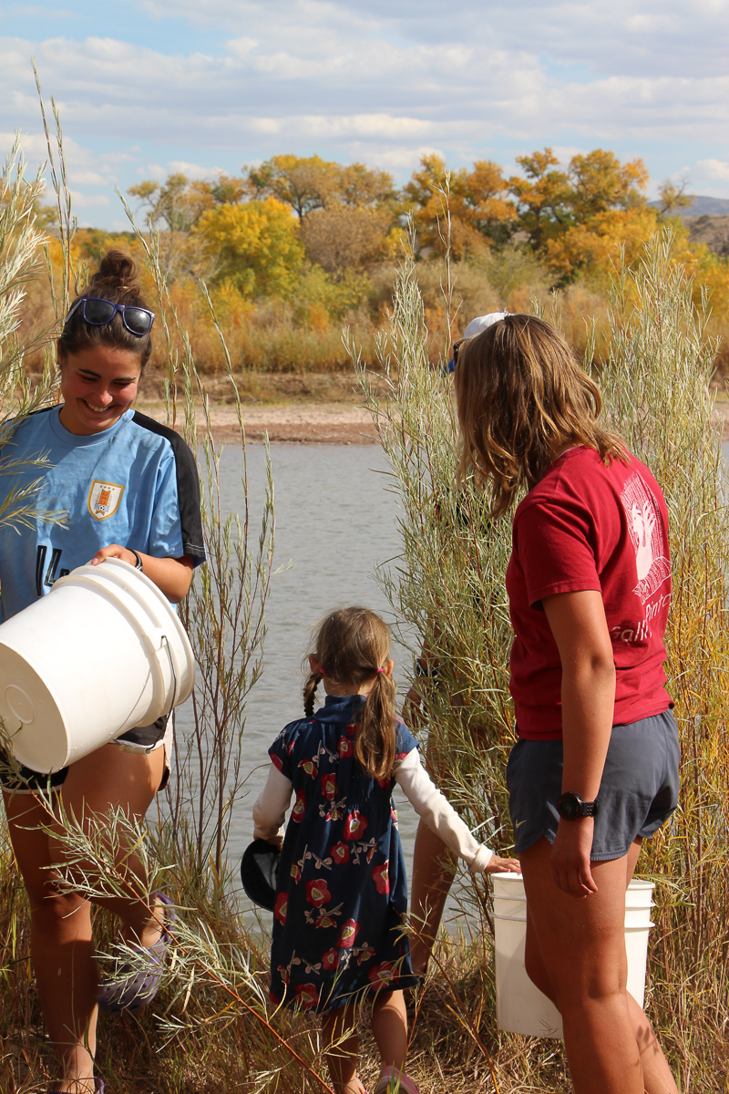 Hannah and Signe help the littlest westie (Esmé Arbetan) release silvery minnow in the Rio Grande