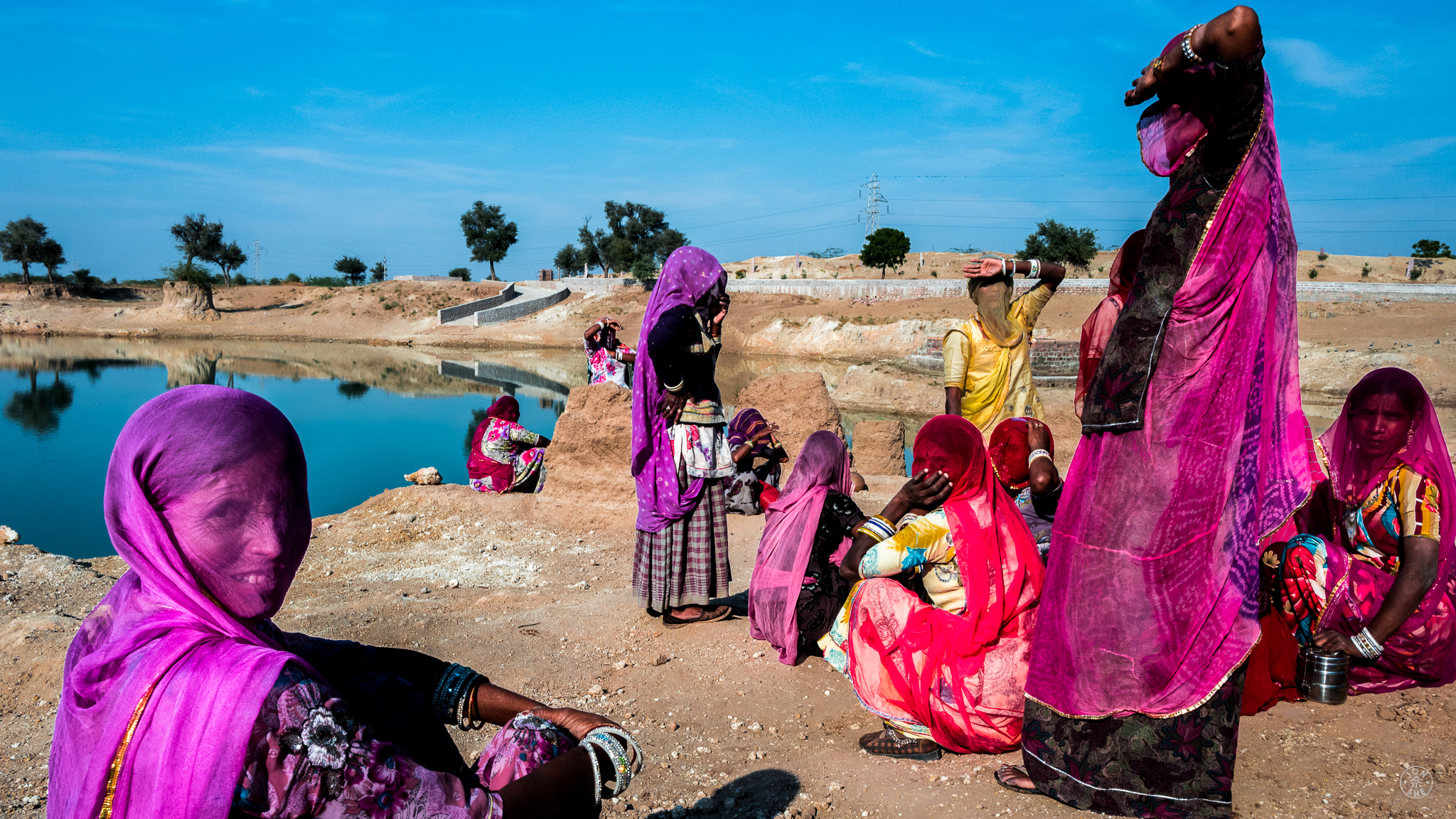 """The Ladies of the Lake"".  Rajahstan, India. January 2017. © Jon She. Leica Q, Leica Summilux 28mm f/1.7 ASPH. We came across this group of lady construction workers in their traditional colorful saris working on a civic project just outside Jodhpur."