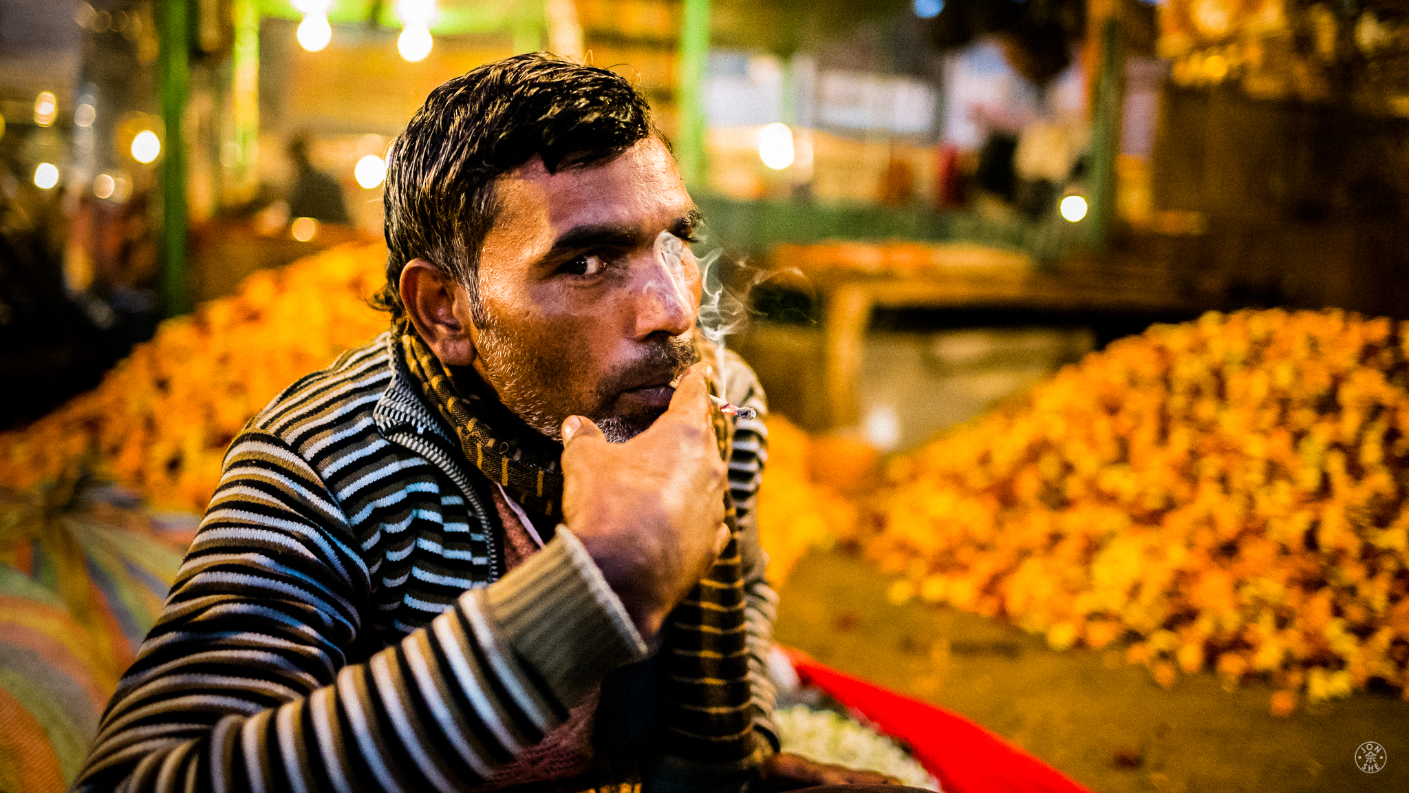 """Flower Market Smoke Break"".  Delhi, India. January 2017. © Jon She. Leica M10, Leica Summilux 28mm f/1.4 ASPH. Another photo from my visit to one of the flower markets in Delhi. This one is of a laborer taking a cigarette break between hauling massive bales of flowers used for Hindu temple prayers."