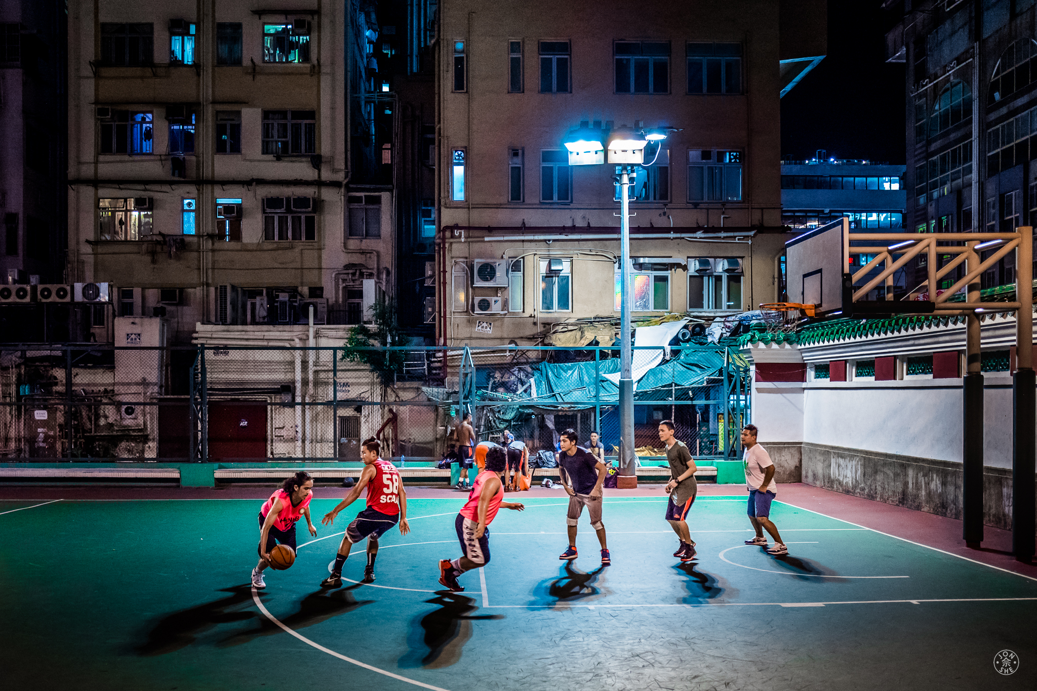 """""""Late Game"""". I came upon this group of young men playing basketball on a court in the middle of a cluster of old apartment buildings, late in the evening. I tried to have a decent depth of field in order to get details of the buildings in the backdrop, while still having an aperture wide enough for a shutter speed to capture the moving players. Kowloon, Hong Kong, China. June 2016. Leica Q (Typ 116), Leica Summilux-M 28mm ASPH. © Jon She."""