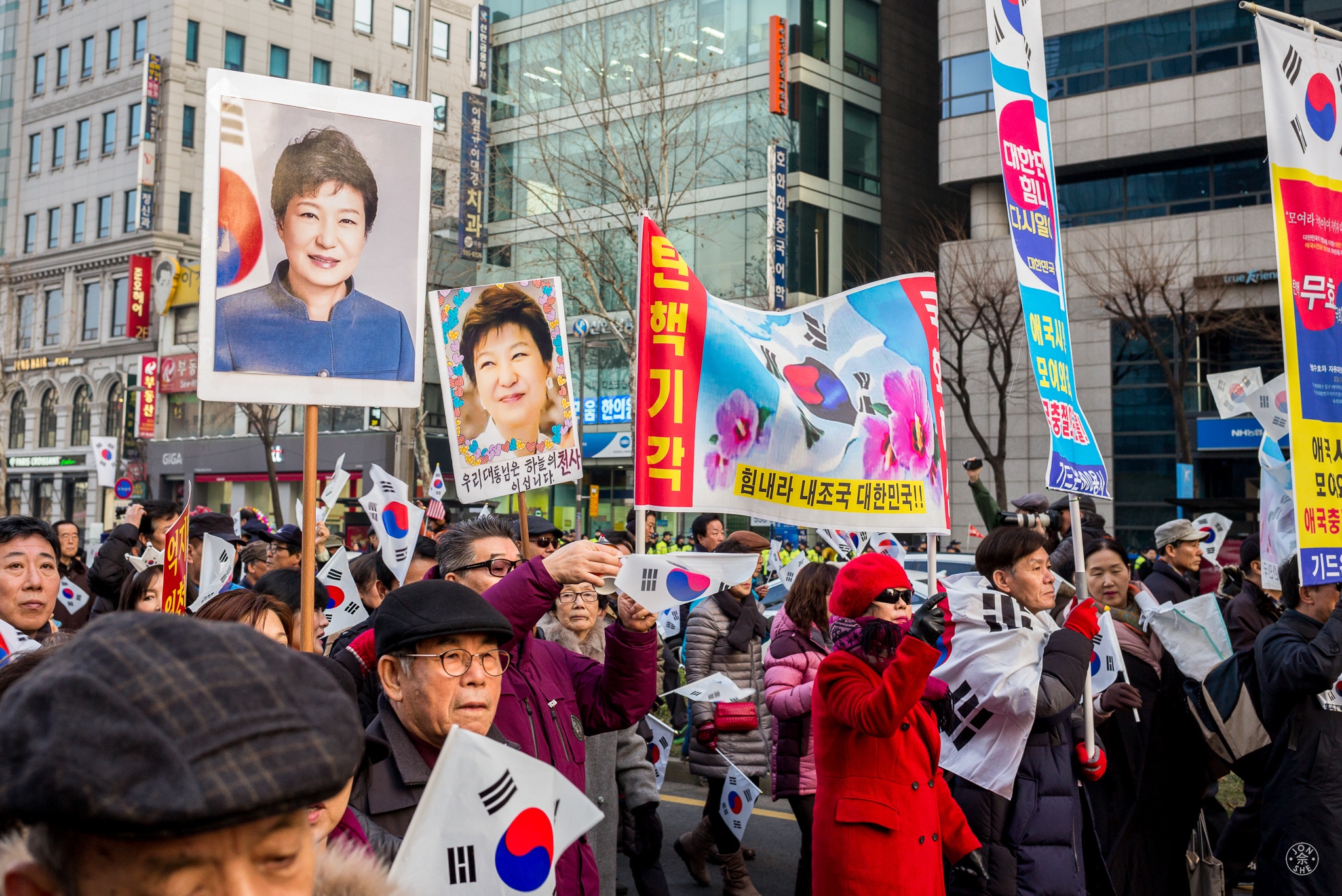 """""""The Lady in Question"""".  Tens of thousands of the republic's citizens marching in protest in Gangnam, the fashionable district of Seoul.There were demonstrators both for and against President Park Geun-hye to be ousted from office for her alleged role in the corruption scandal that had gripped Korea for several months. Seoul, South Korea.January 2017. © Jon She.Leica M-P (Typ 240), Leica Summilux-M 35mm f/1.4 ASPH (FLE)."""