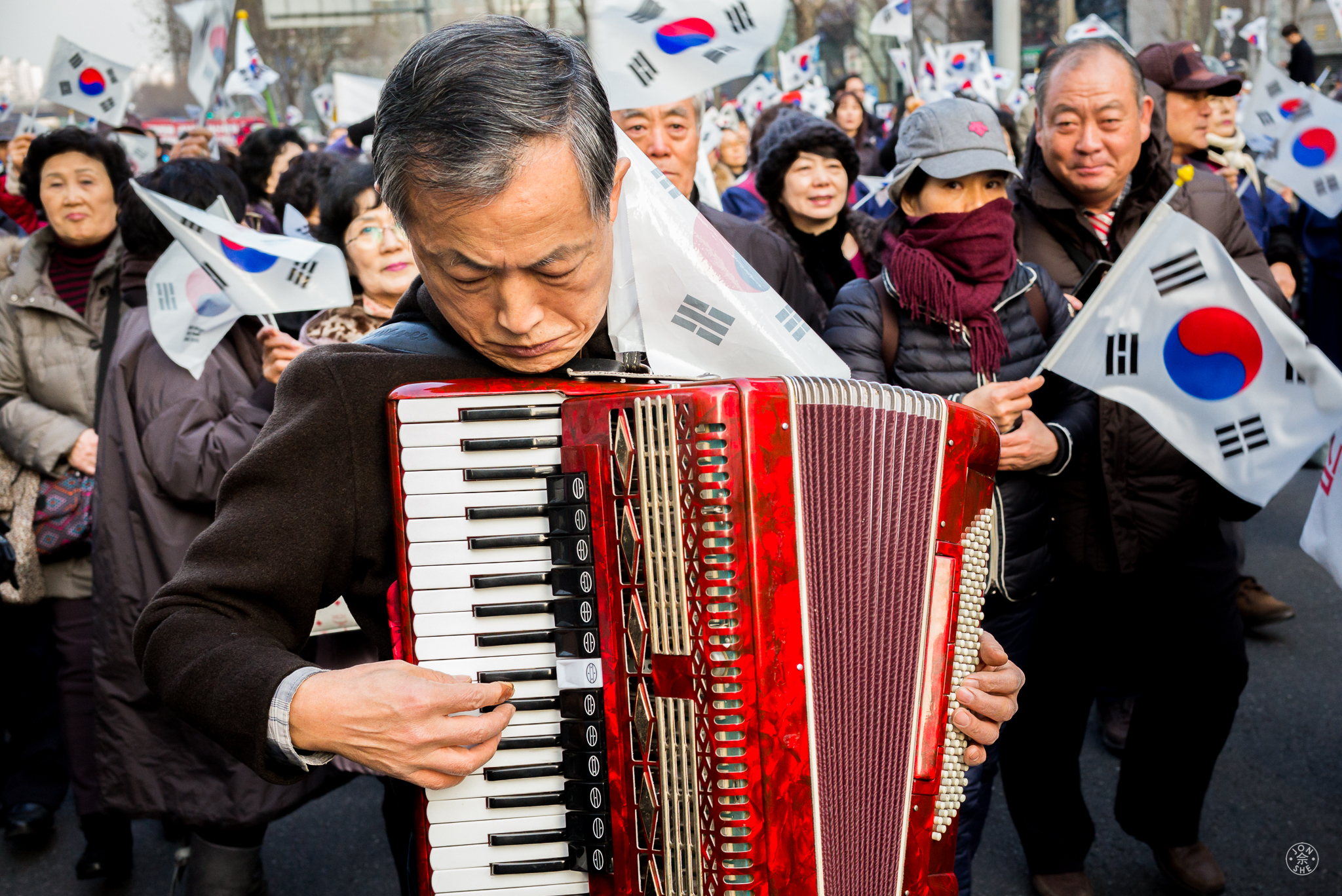 """""""The Music of Protest"""".  A Korean gentleman plays his accordion to voice his protest, in a peaceful demonstration attended by tens of thousands of the republic's citizens in Gangnam, the fashionable district of Seoul. Seoul, South Korea.January 2017. © Jon She. Leica M-P (Typ 240), Leica Summilux-M 35mm f/1.4 ASPH (FLE)."""