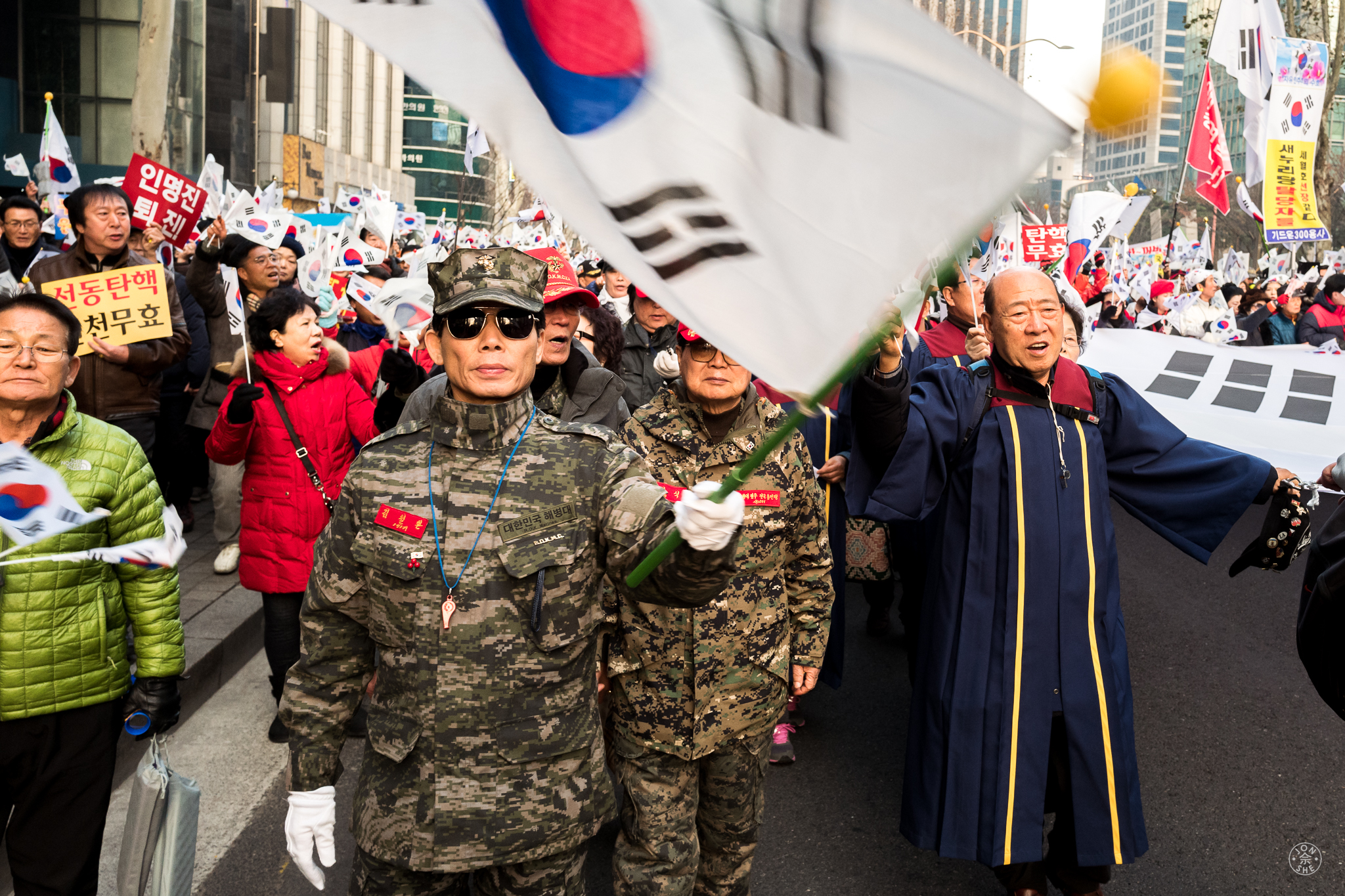 """""""We're All In This Together"""". Soldiers, priests, and academicians marched shoulder-to-shoulder, in a peaceful demonstration attended by tens of thousands of the republic's citizens in Gangnam, the fashionable district of Seoul. There were demonstrators both for and against President Park Geun-hye to be ousted from office for her alleged role in a corruption scandal. Seoul, South Korea. January 2017. © Jon She. Leica Q (Typ 116), Leica Summilux 28mm f/1.7 ASPH (FLE)."""