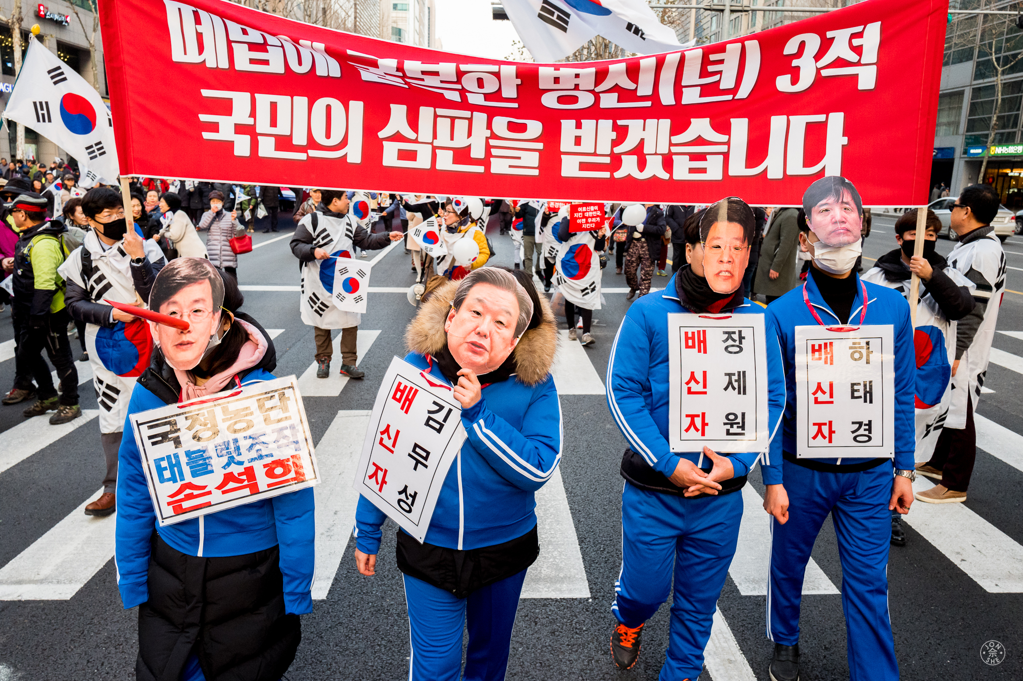 """""""Caricatures of Protest"""". Demonstrators dress in caricatures of allegedly corrupt officials during a mass rally to both call for and against President Park to be ousted from office for her alleged role in a corruption scandal. Seoul, South Korea. January 2017. © Jon She. Leica Q (Typ 116), Leica Summilux 28mm f/1.7 ASPH (FLE)."""