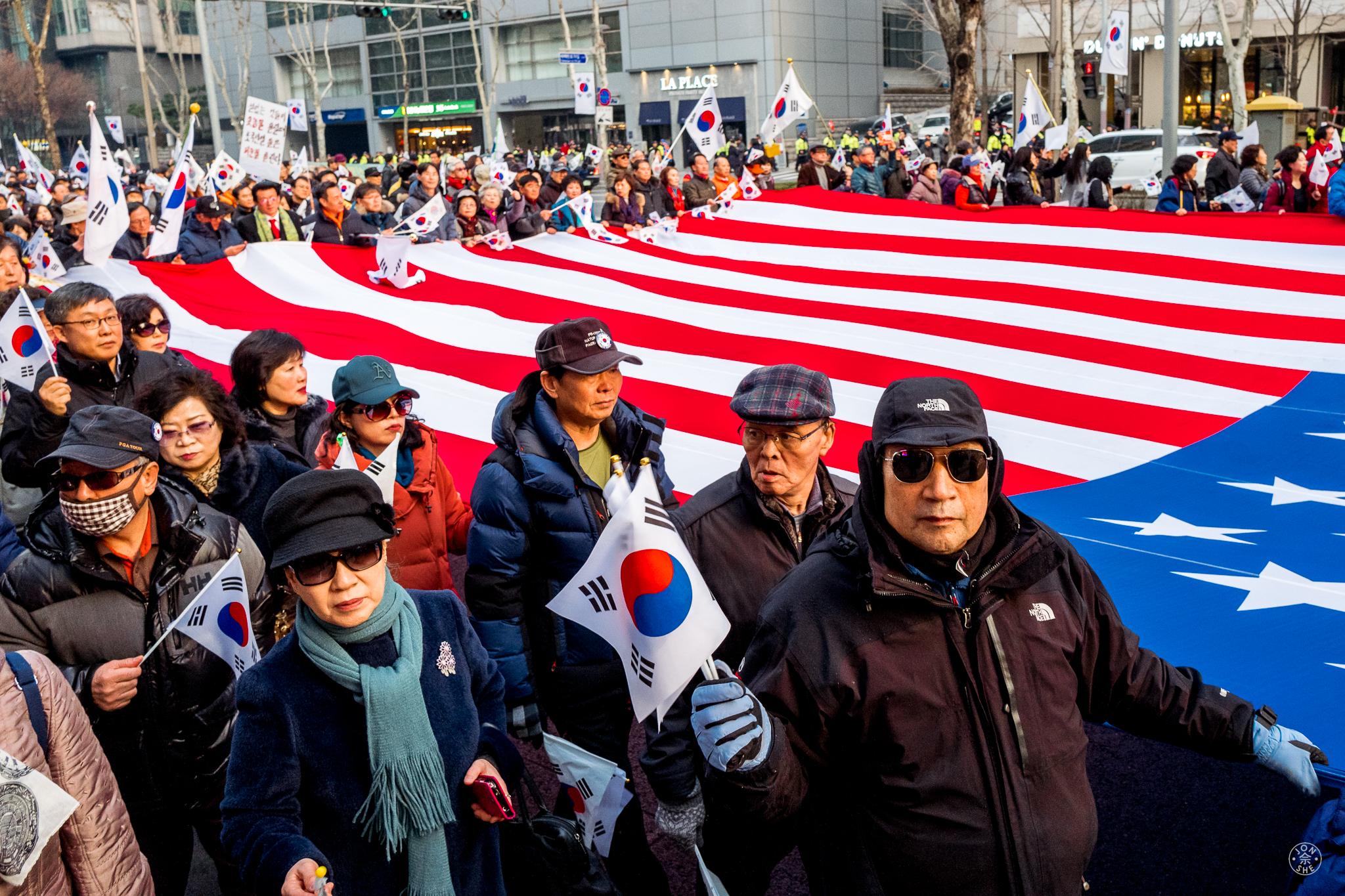 """""""What'cha Looking At?"""".  Tens of thousands of the republic's citizens attended peaceful protests to either call for, or against, President Park to be ousted from office for her alleged role in a corruption scandal that had gripped Korea for months. The importance that Koreans attribute to their relationship with the USA can be seen in the number of US flags carried, alongside the Korean one. Seoul, South Korea. January 2017. © Jon She. Leica Q (Typ 116), Leica Summilux 28mm f/1.7 ASPH (FLE)."""