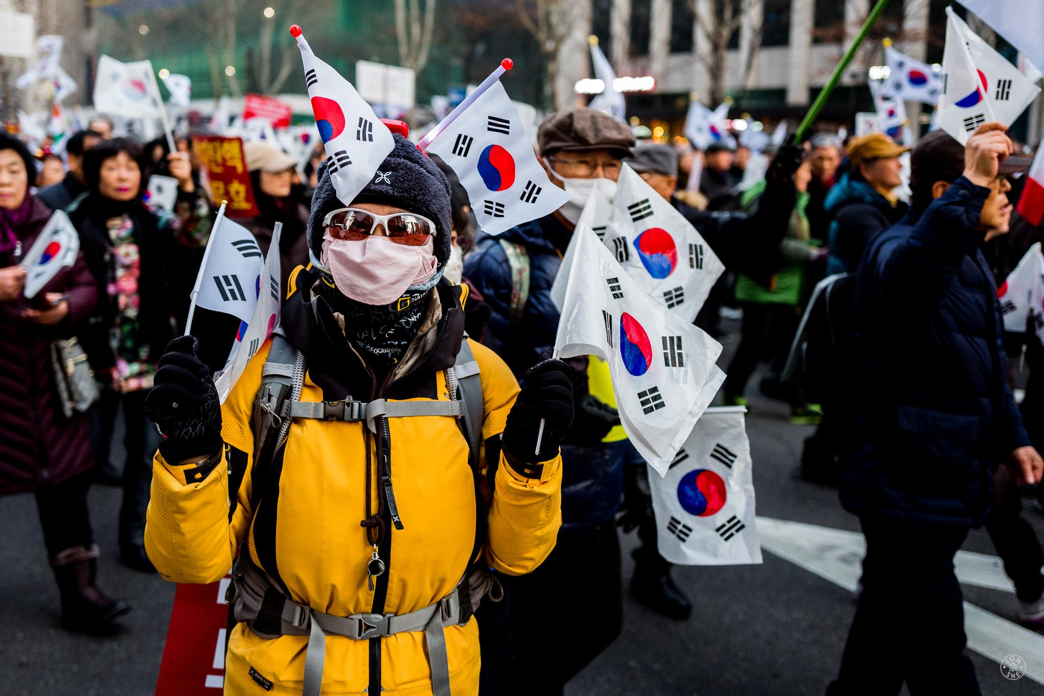 """Gangnam Carnivale (1)"". Peaceful demonstrations appear to take the place of a festive Carnivale in Seoul.Seoul, South Korea. January 2017. © Jon She. Leica Q (Typ 116), Leica Summilux 28mm f/1.7 ASPH (FLE)."