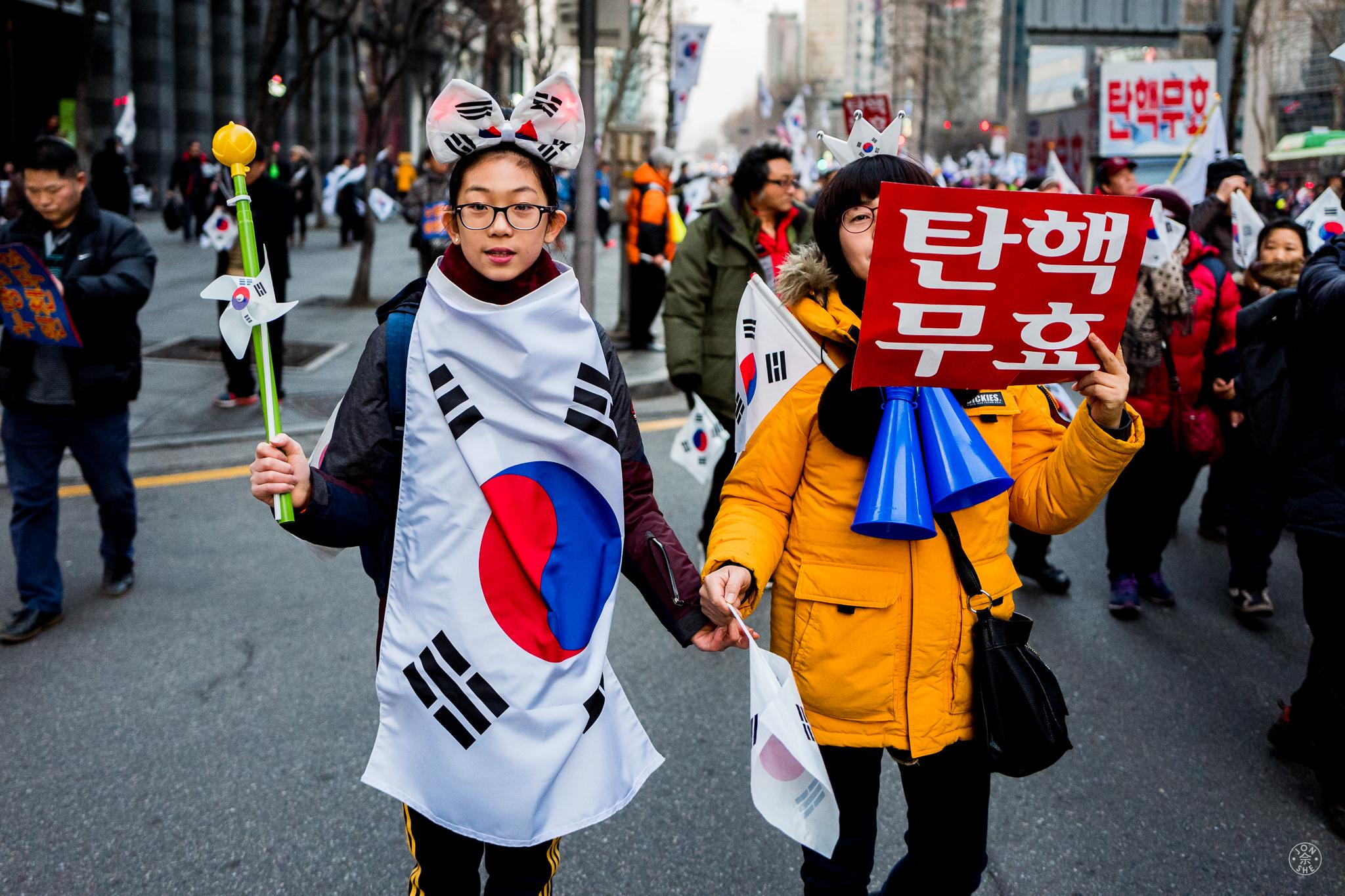 """Gangnam Carnivale (3)"". Peaceful demonstrations appear to take the place of a festive Carnivale in Seoul.Seoul, South Korea. January 2017. © Jon She. Leica Q (Typ 116), Leica Summilux 28mm f/1.7 ASPH (FLE)."