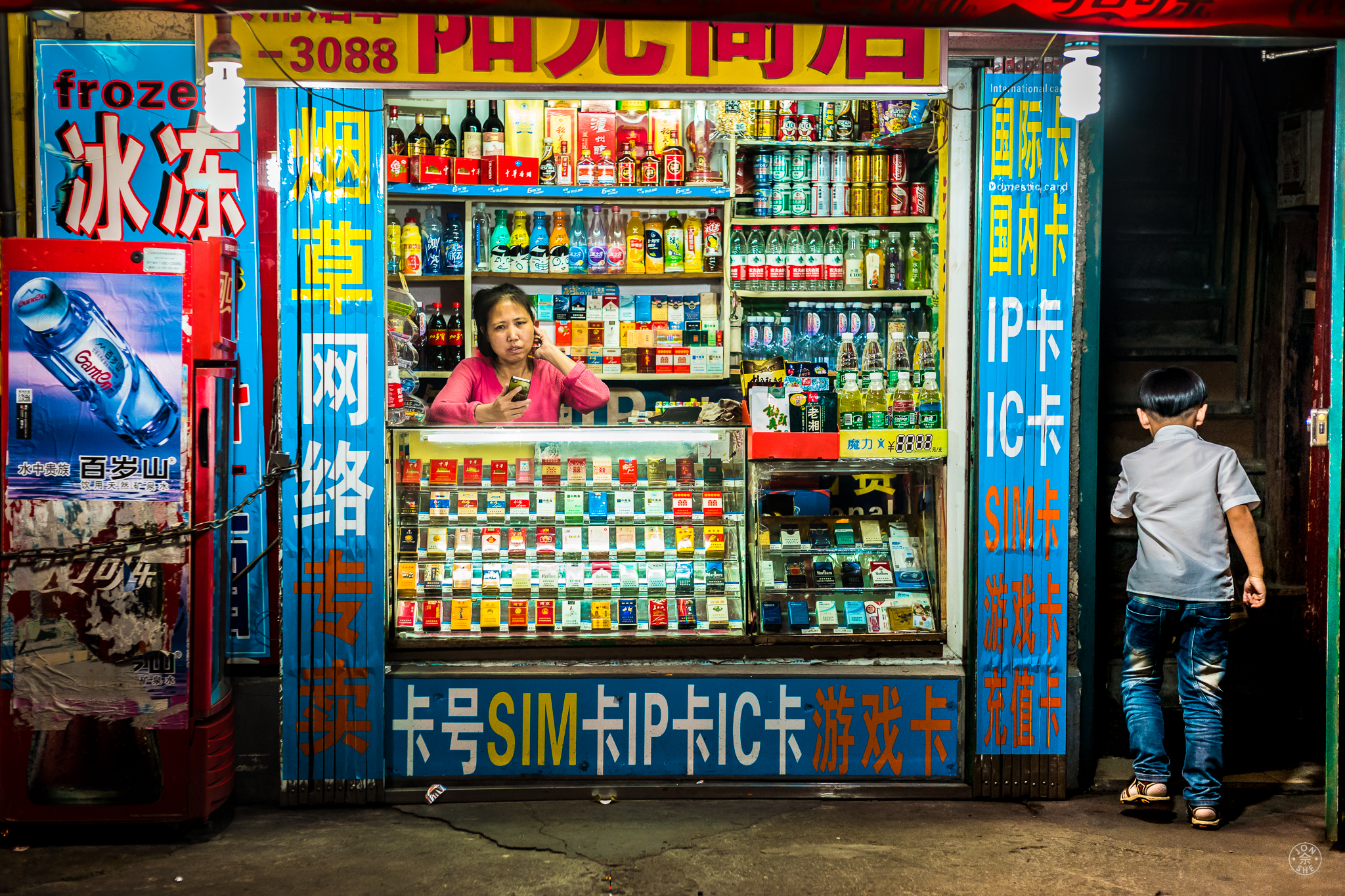 """""""The Night Store"""".  An irate storekeeper yells at her young son to go up to bed, in their home above their tobacco and sundries shop, late at night. Shanghai, China.May 30, 2016. © Jon She.Leica SL (Typ 601), Noctilux-M 50mm ASPH."""