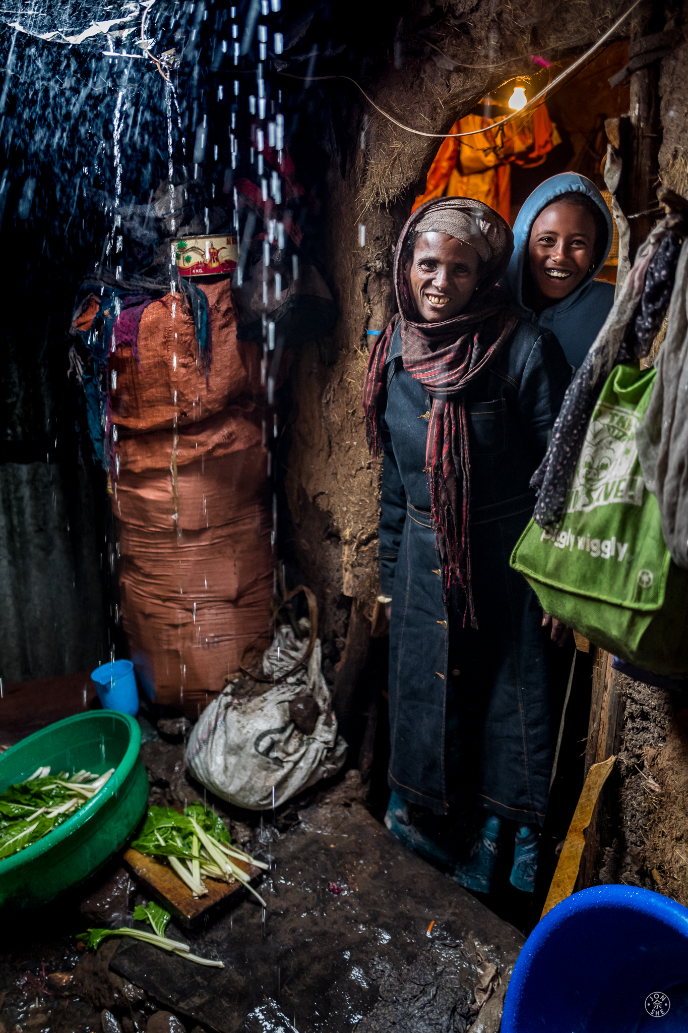 I was very touched by the warm hospitality extended to me by some of Strong Hearts' clients. This lady and her teenage daughter welcomed me into their one room windowless shack for a cup of coffee and for shelter from the torrential rain that day. They were preparing food on the ground of the alleyway just outside their doorway. Addis Ababa, Ethiopia. © Jon She 2017.