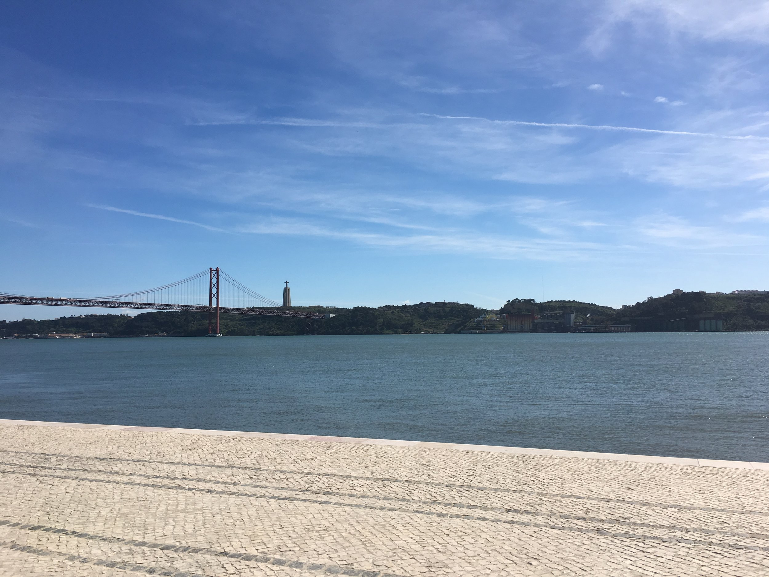 The Tagus river looking across the Ponte 25 de Abril suspension bridge to the statue of Cristo Rei