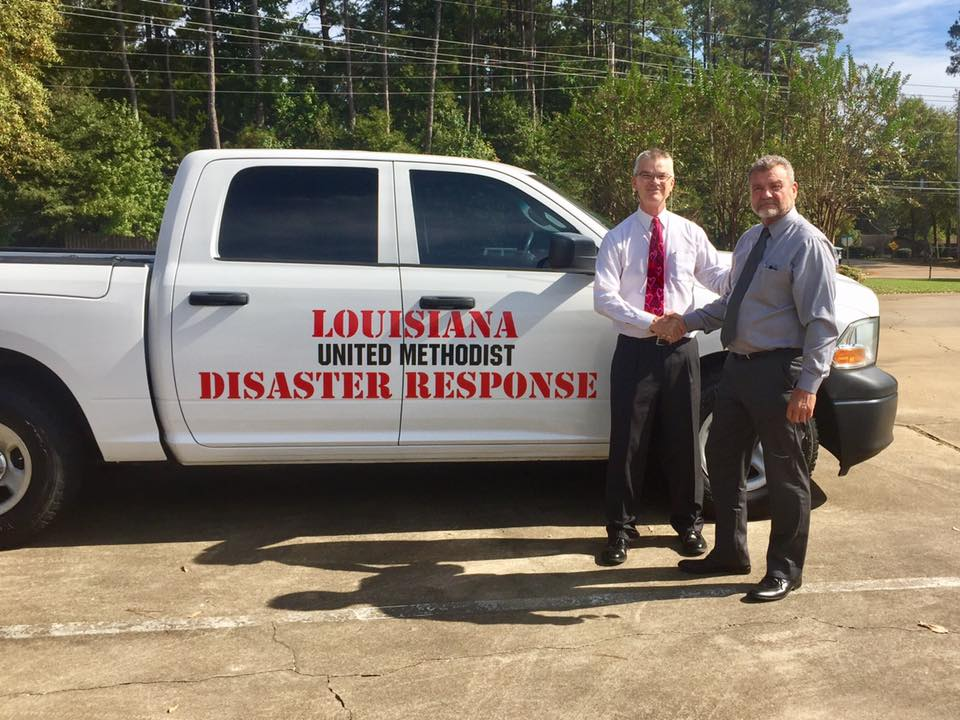 Rev. Bob Deich, left, thanks Bob Carrell, right, representing the United Methodist Foundation of Louisiana, for the donation of two cab crew trucks to the La. Conference Disaster Response Team. One of the trucks is pictured here.