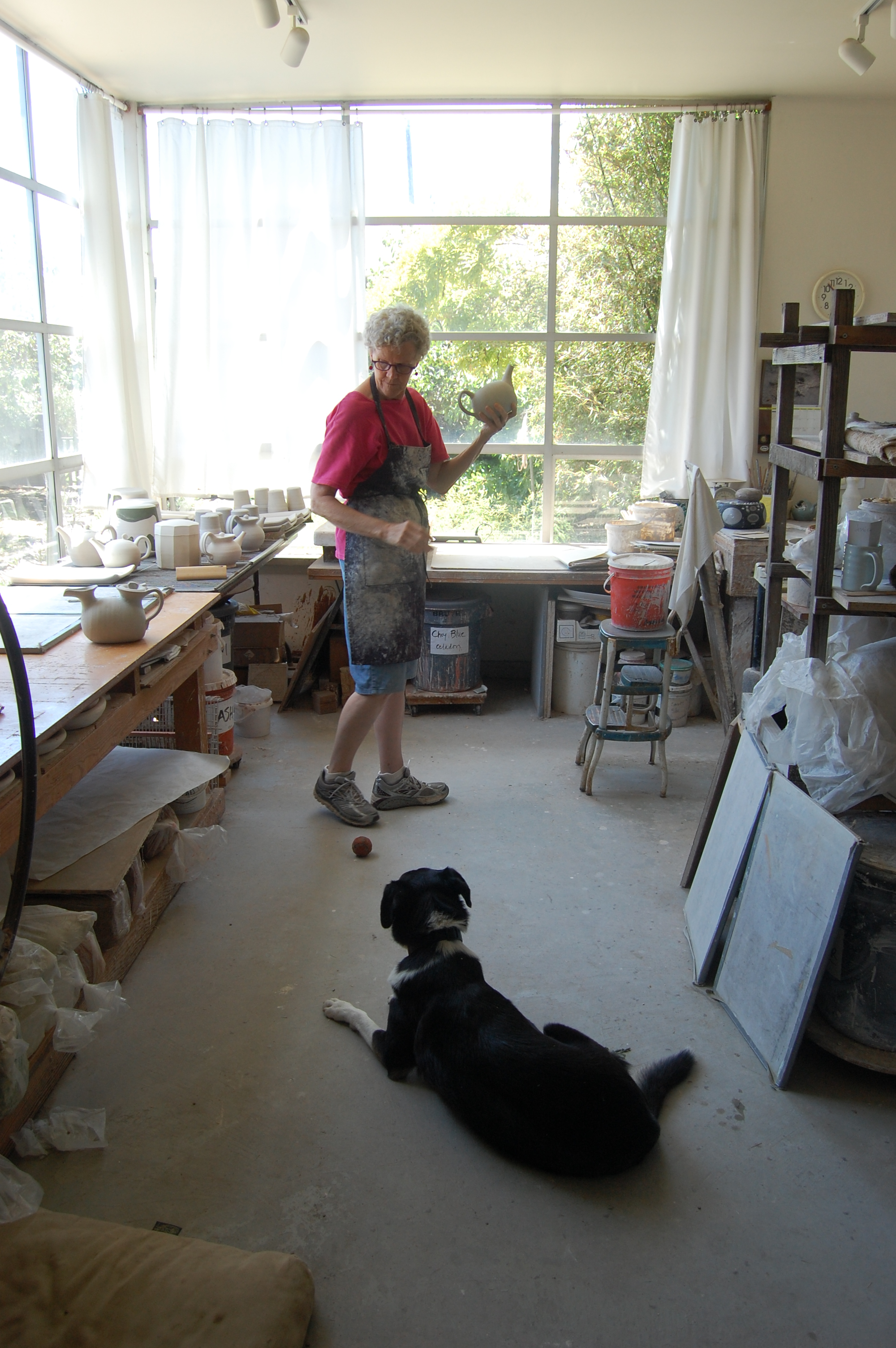 Mary Law in her pottery studio with her faithful but persistent dog, Doc Watson.