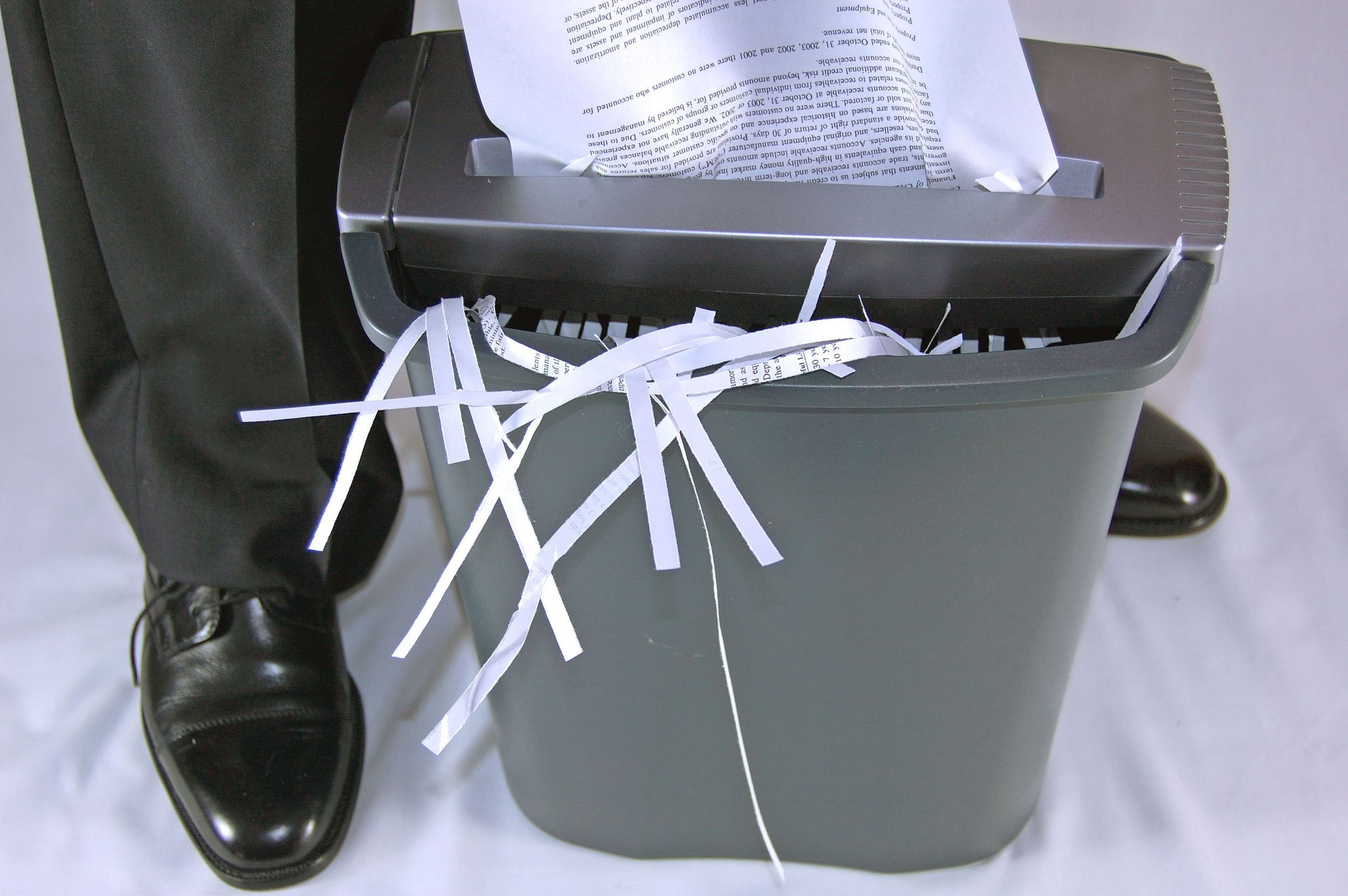 man disposing documents with a paper shredder