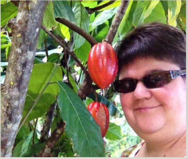 Romi Burks beside a Theobroma Cacao tree