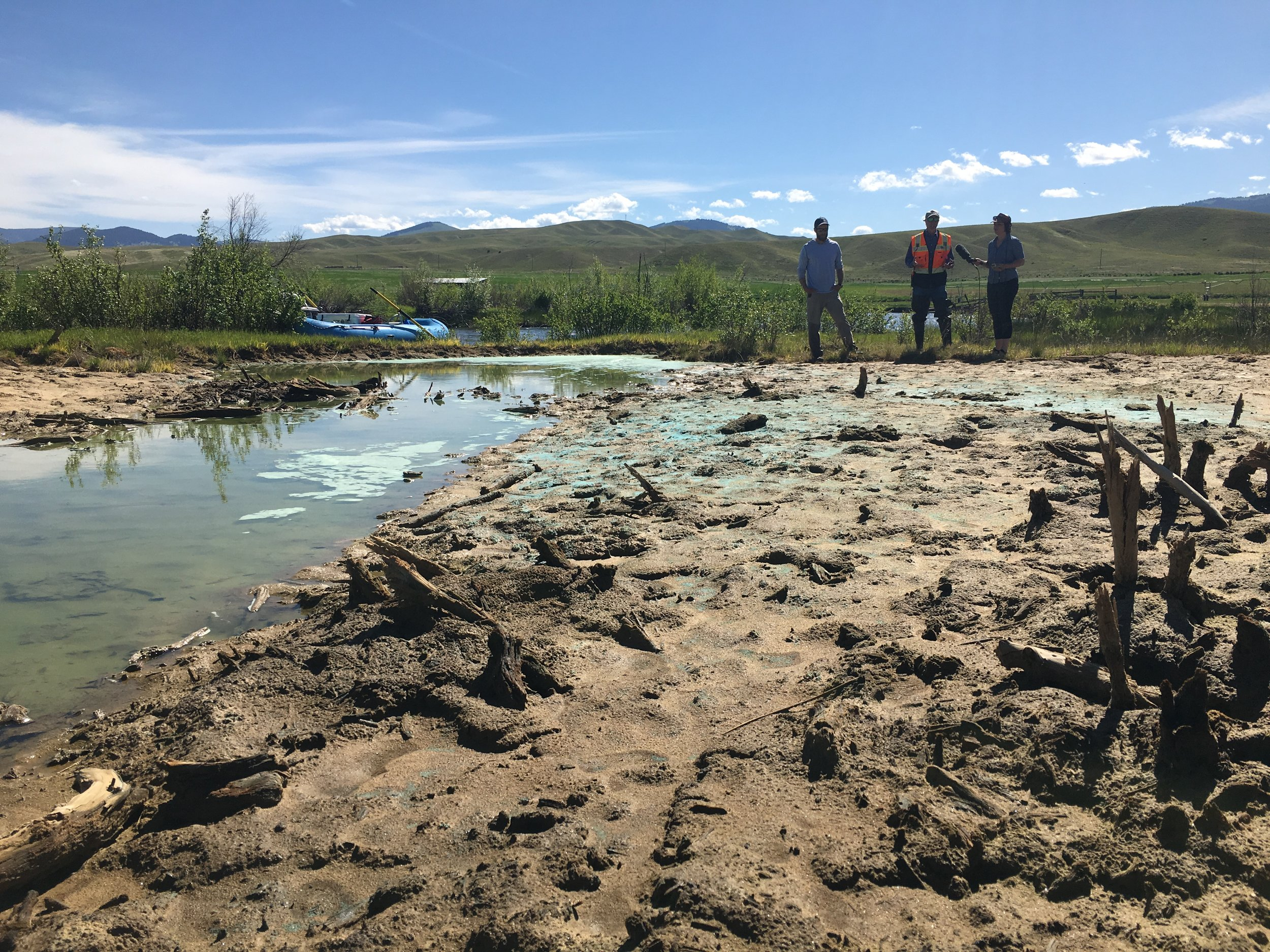 "Alex Leone (Left), Will McDowell (Center) and Nora Saks (Right) look over a contaminated embankment on the Upper Clark Fork River near Warm Springs. Known as a ""slickens"" areas like this are common along unremediated stretches the river, the blue pigments are copper sulfides leaching up through the tailings."