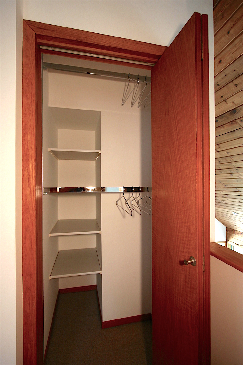 """All of the built-in closets in Solace House feature fully-adjustable commercial clothes rod hardware (making """"double-racking"""" such as shown here an easy option)."""