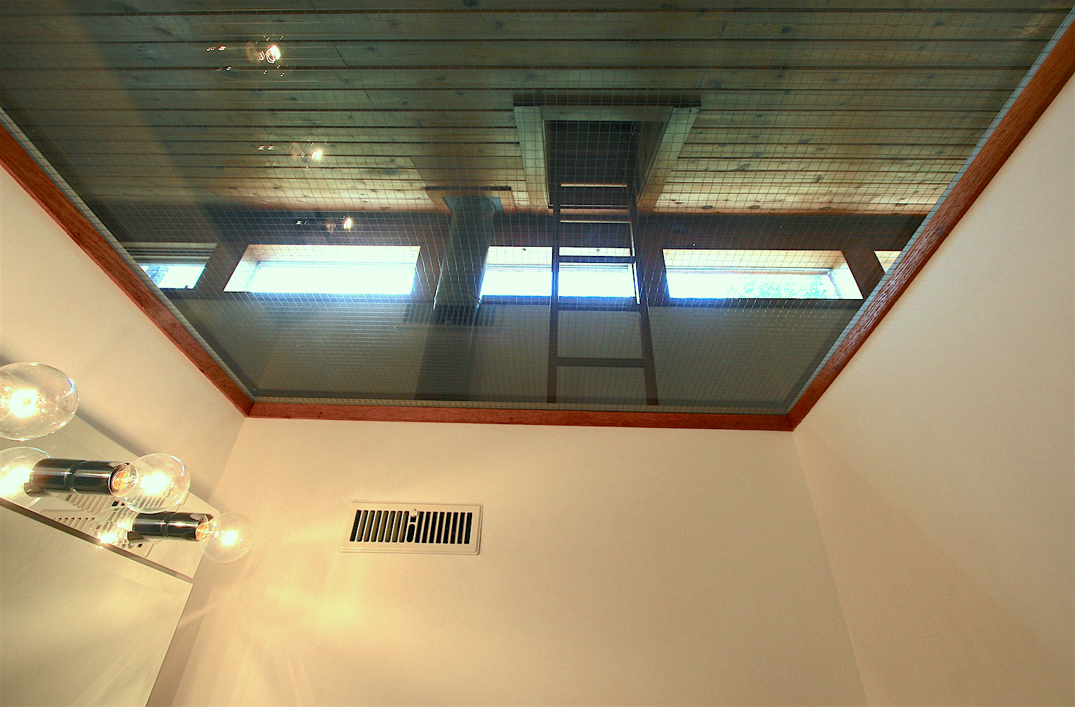 """The ceiling of the two-piece bath is made of wire-reinforced tempered glass, allowing in natural light from the clerestory windows. The upper ladder to the """"Eagle's Nest"""" can be seen above..."""