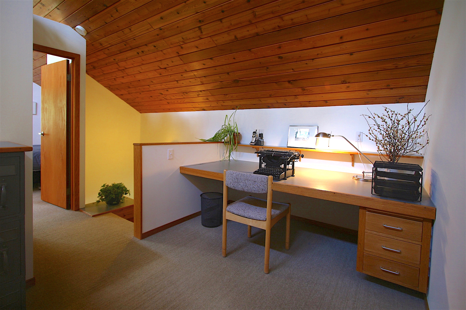 The studio/library features a large, built-in work surface against the north wall (discretely reinforced with steel, it supports full body weight and more). The stairwell to the lower level is just to the left of the knee-wall...