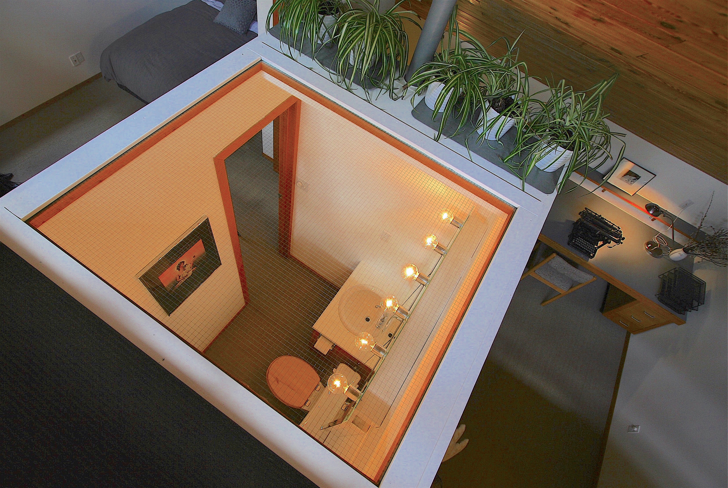 The  sleepspace  and the studio/library on the upper level are separated by a glass-ceilinged bathroom...