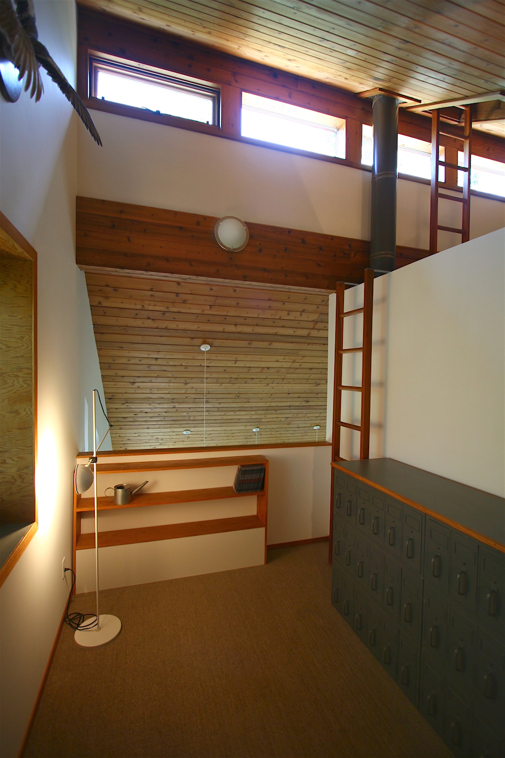 """The studio/library looks down to the dining area below. The """"ship's ladders"""" lead up through a hatch in the roof to the """"Eagle's Nest""""..."""