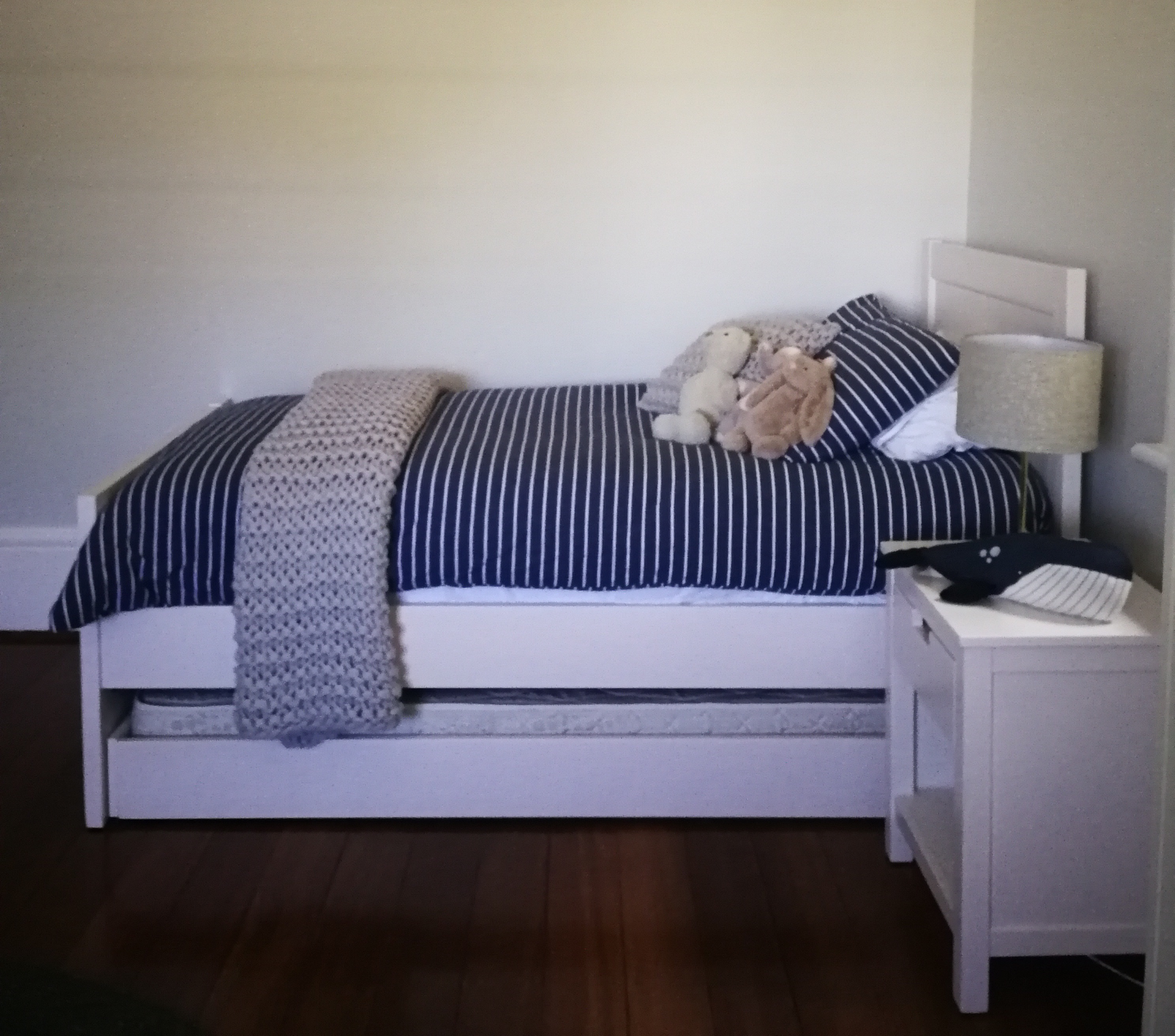The white painted furniture contrasts beautifully against the original jarrah floorboards. A little nightstand holds precious things and a lamp for bedtime stories. The bed, from Out of the Cot, has removeable side rail and a trundle for future sleepovers.