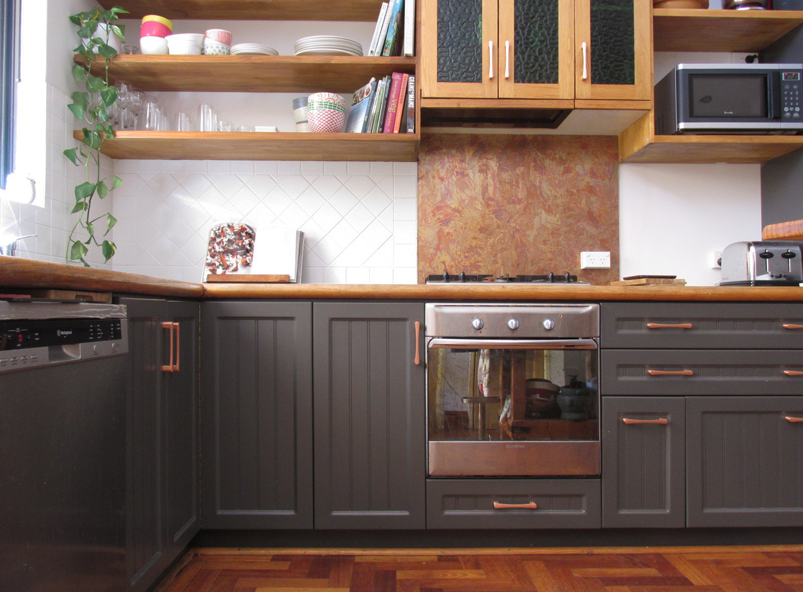 The renovated kitchen with its painted cupboard fronts and tiles and new solid timber shelving.